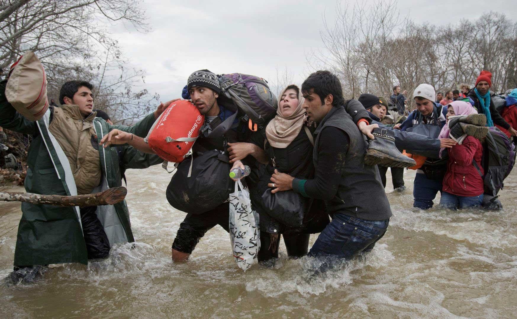 A woman is supported by two men while crossing a river, as refugees attempt to reach Macedonia on a route that would bypass the border fence, on March 14, 2016.