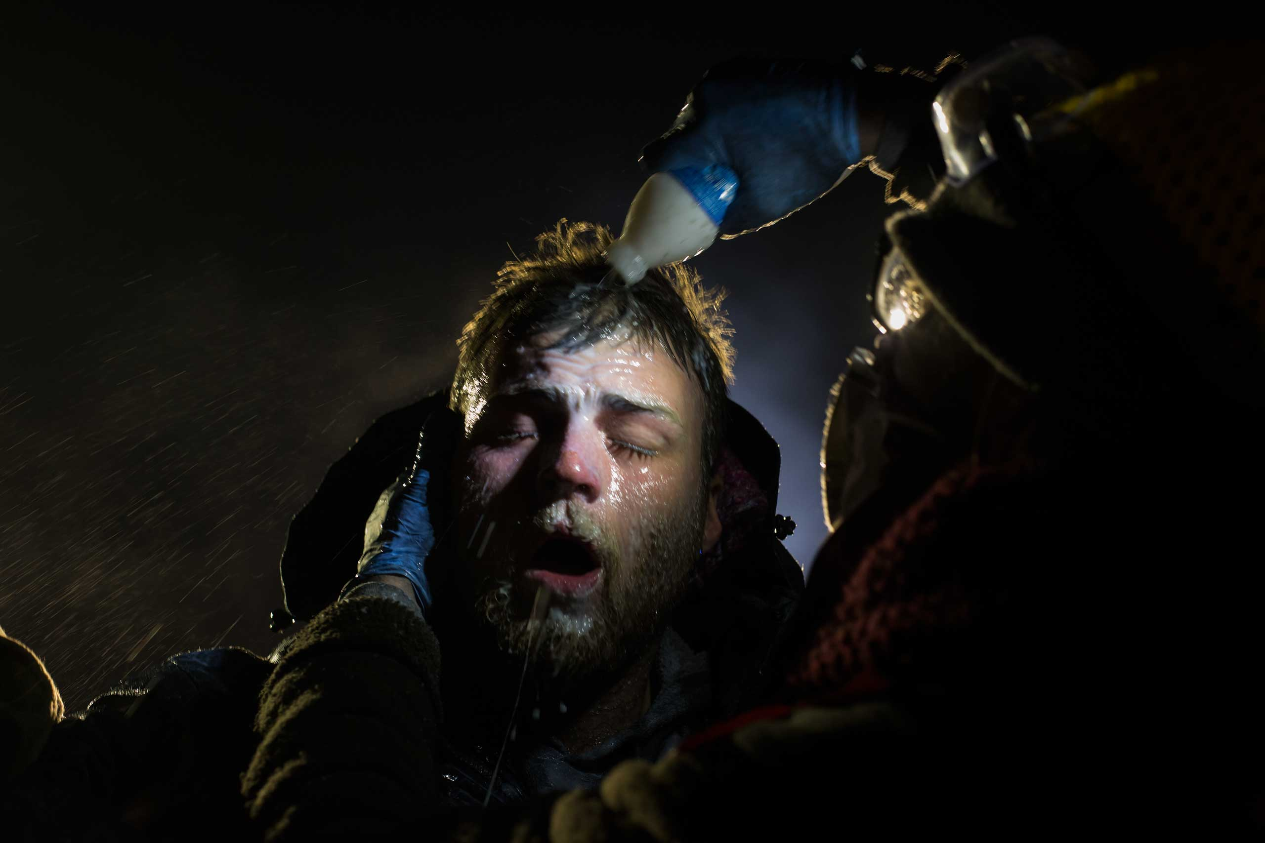 Healers - A man is treated after being pepper sprayed by police. White people have joined the camps in large numbers, often standing in front of indigenous protestors to shield them with their bodies.