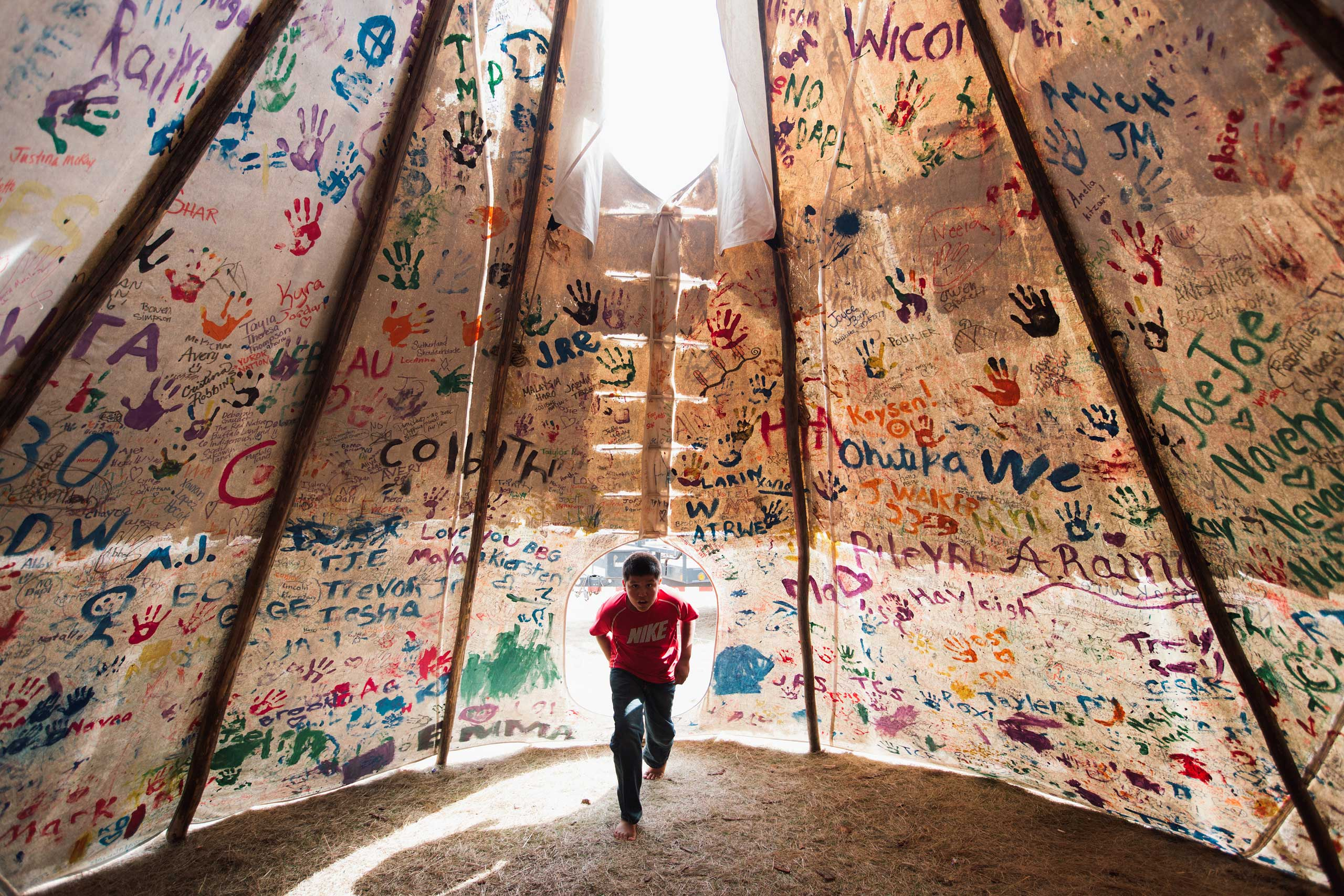 Jesse Jaso, 12, enters the Unity Teepee, at the Sacred Stone Camp near Cannonball, N.D. on Sept. 10, 2016. The teepee is signed by camp supporters from all over North America and around the world.