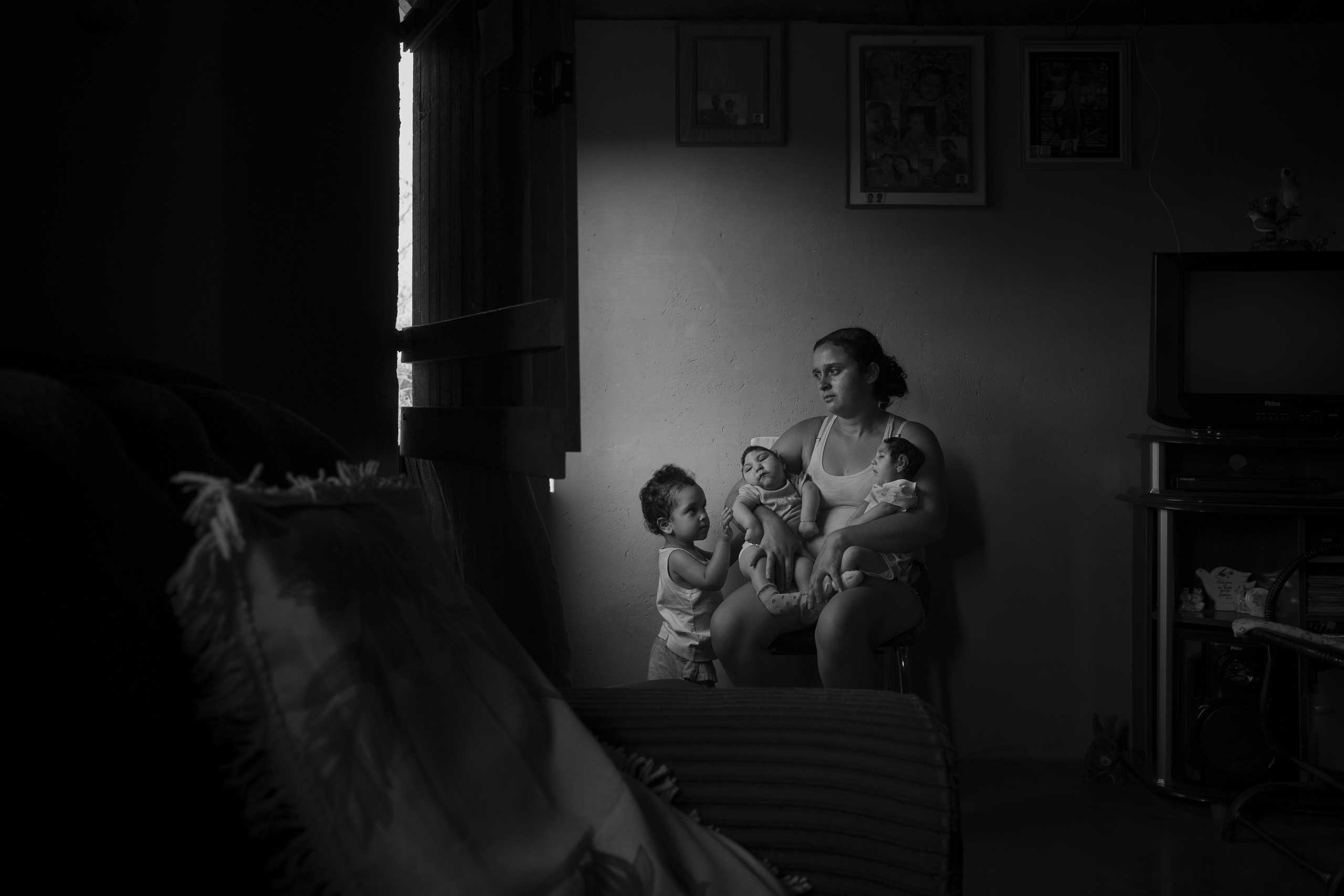 Marcela, 2, observes her sisters in her mother's lap at the family's home in the rural area of Areia. Twin sisters Heloisa (left) and Heloá (right) were born seven months prior with microcephaly caused by the Zika virus.
