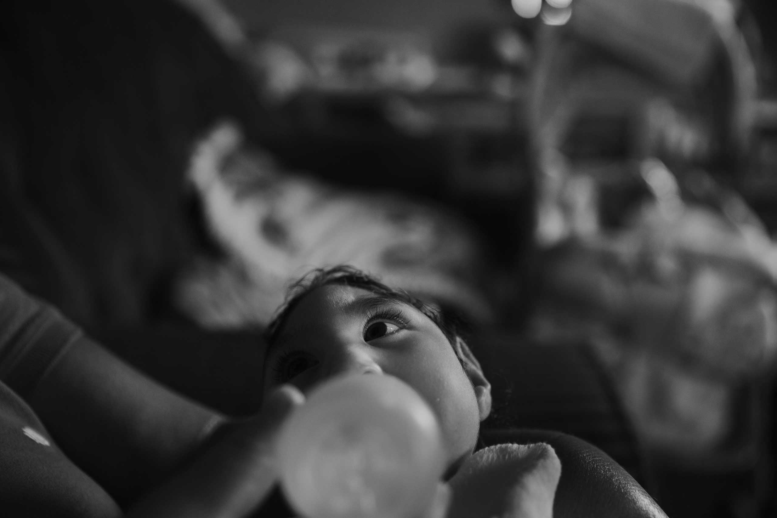 Heloá, seven months old, takes a bottle of milk on her grandmother's lap at the family's home in Areia. She and her sister Heloísa were born with microcephaly caused by the Zika virus.