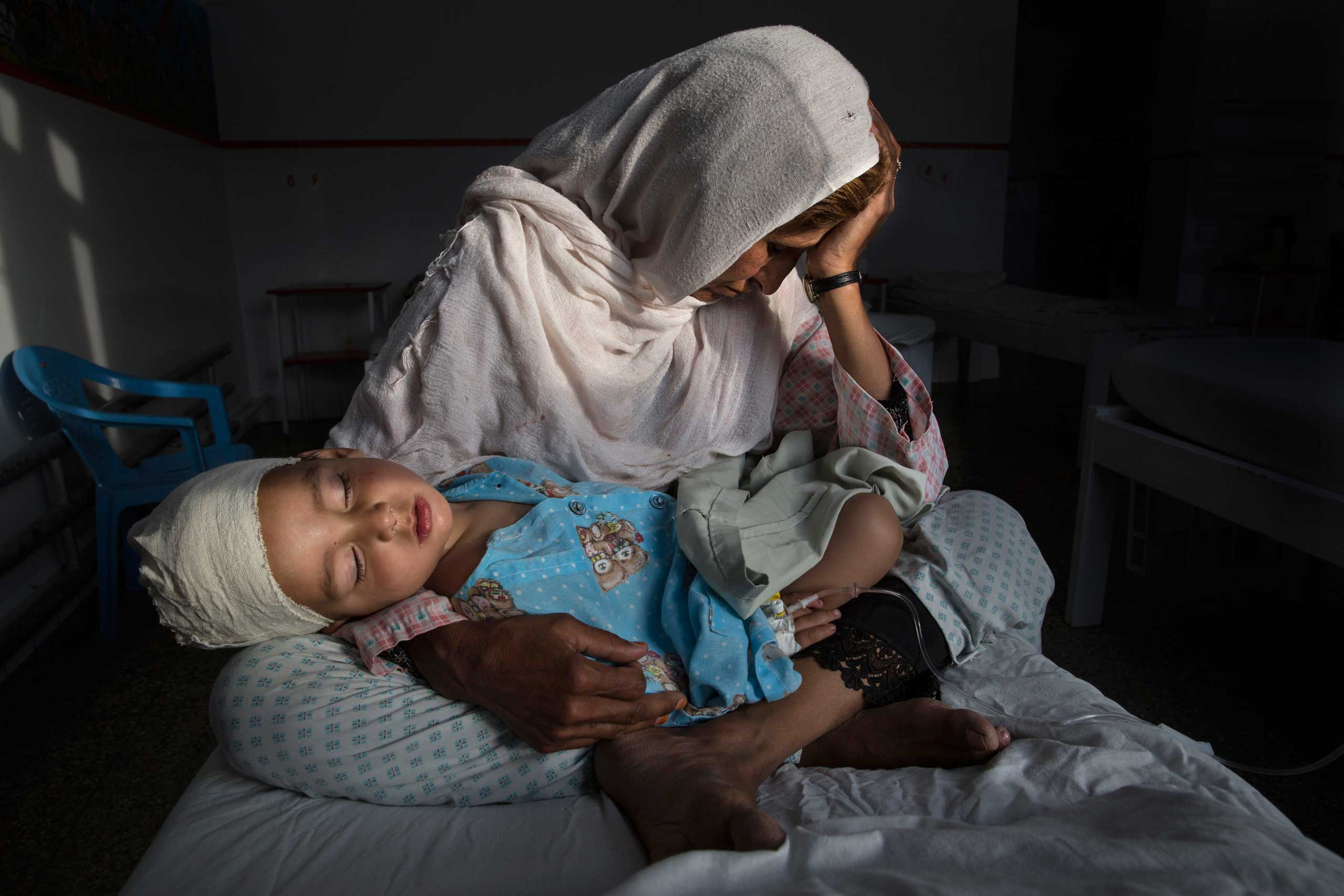 At the hospital, Najiba holds her two-year-old nephew Shabir who was injured from a bomb blast in Kabul on 29 March 2016.