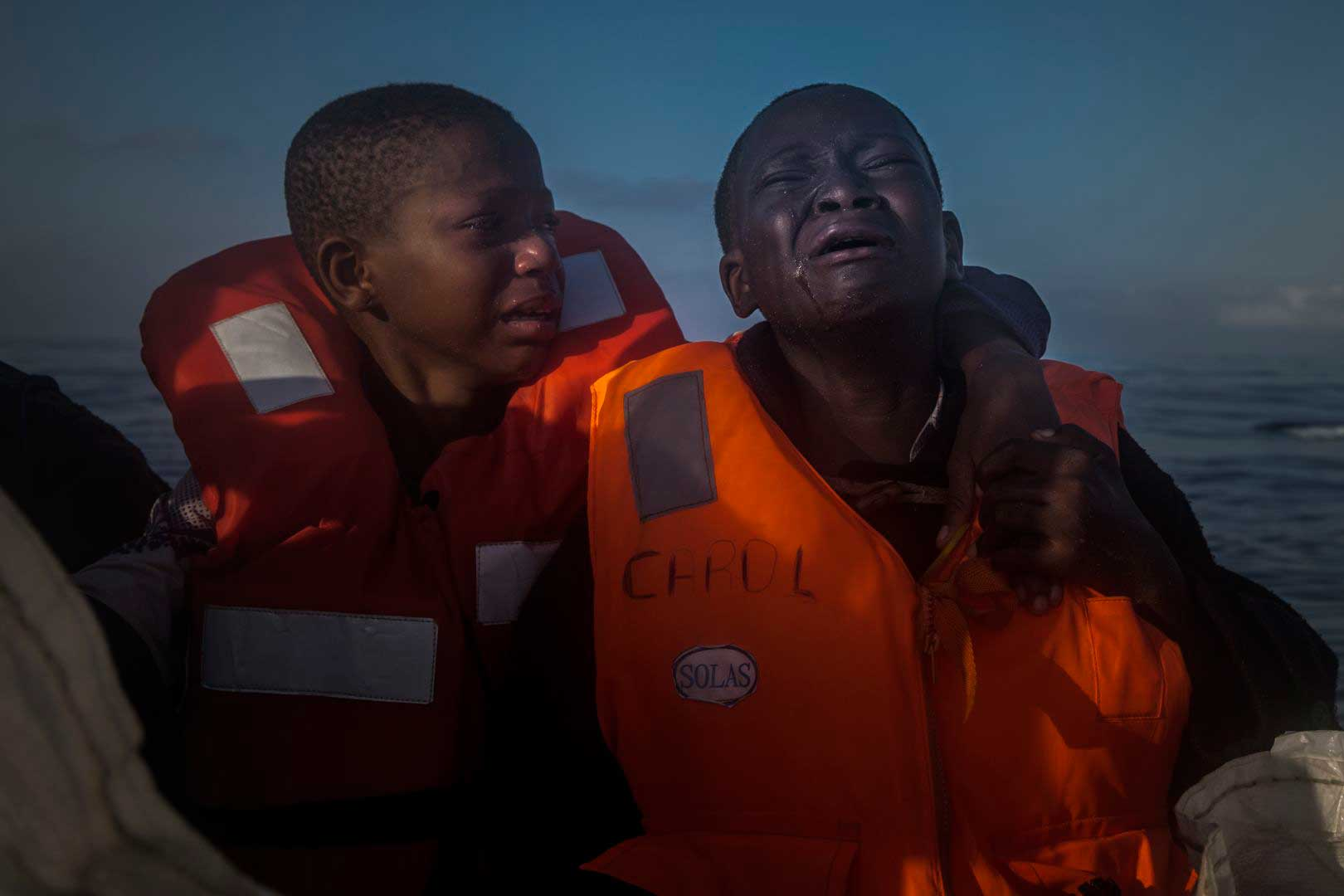 An 11-year-old girl from Nigeria (left), who said her mother died in Libya, cries next to her 10-year-old brother aboard an NGO rescue boat, on July 28, 2016.