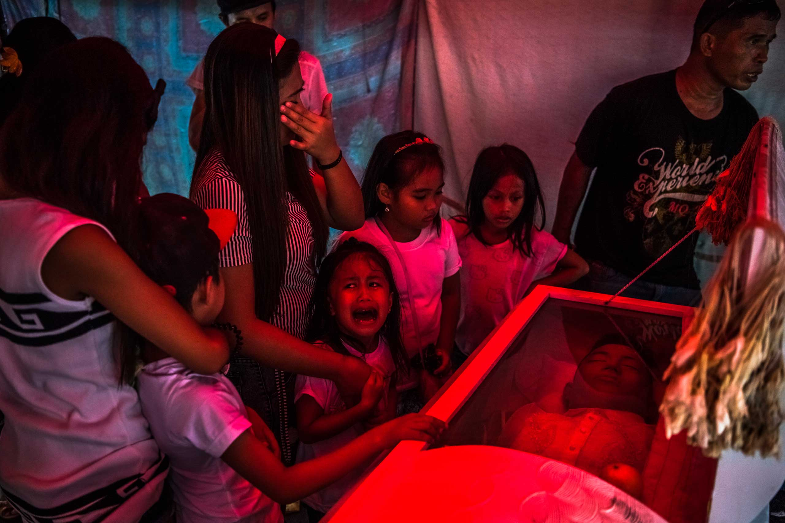 Six-year old Jimji cries in anguish as she screams  papa  before funeral parlor workers, move the body of her father, Jimboy Bolasa, from the wake at the start of the funeral to Navotas cemetery on Oct. 9, 2016 in Manila, Philippines.