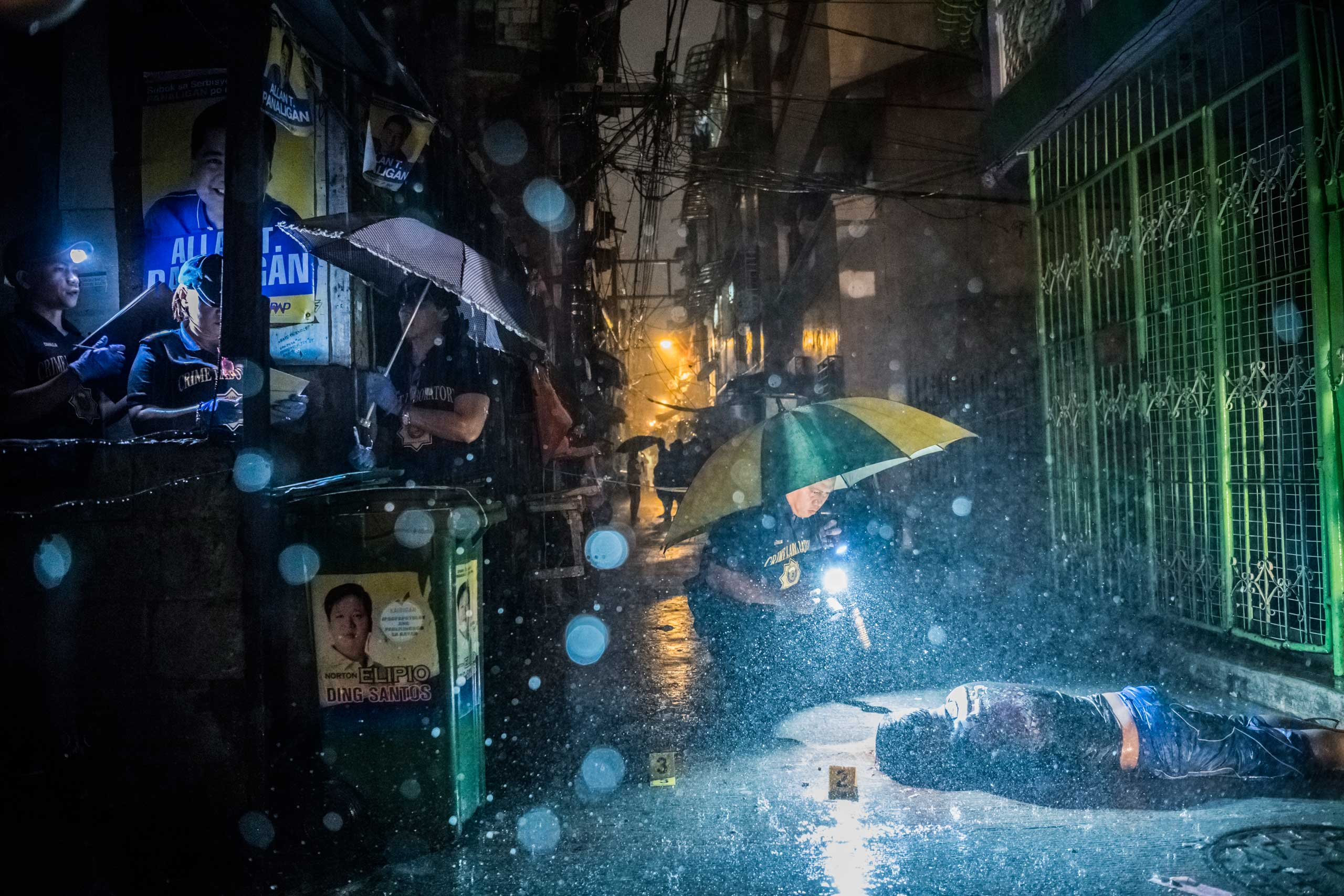 Heavy rain pours as Scene of the Crime Operatives investigate inside an alley on Oct. 11, 2016, where a victim, Romeo Joel Torres Fontanilla, 37, was killed by two unidentified gunmen riding motorcycles in the early morning in Manila, Philippines.