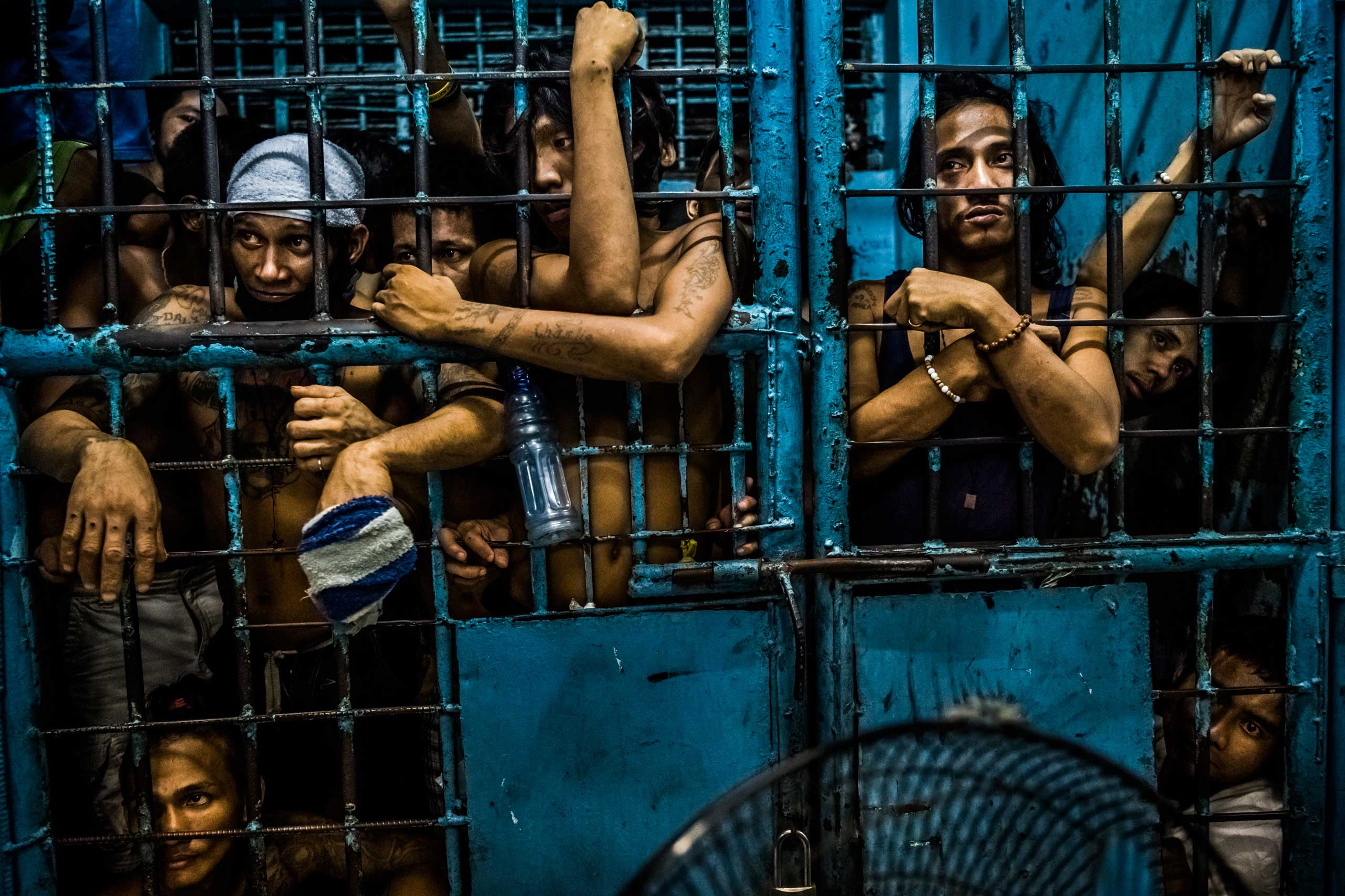 Inmates watch as drug suspects are processed inside a police station on Oct. 12, 2016 in Manila, Philippines.