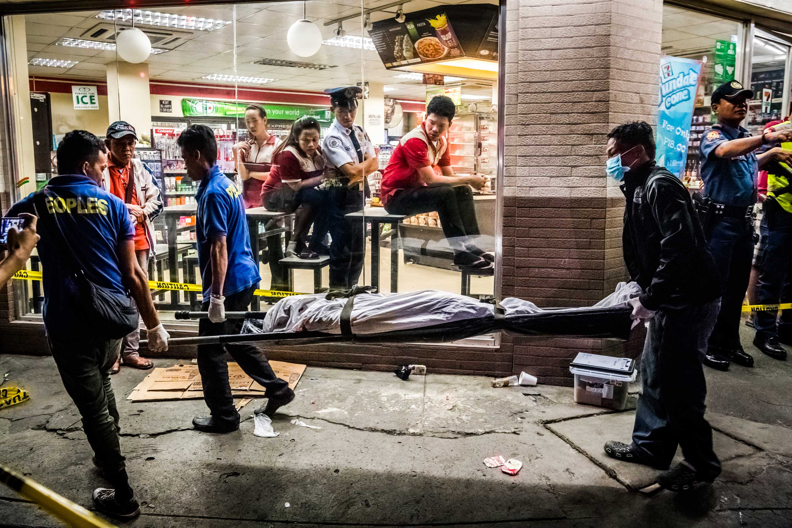 Funeral parlor workers carry away the body of Edwin Mendoza Alon-Alon, 36, who was killed by an unknown gunman on the road in front of a 7-Eleven store in Tambo on Oct. 18, 2016 in Manila, Philippines.