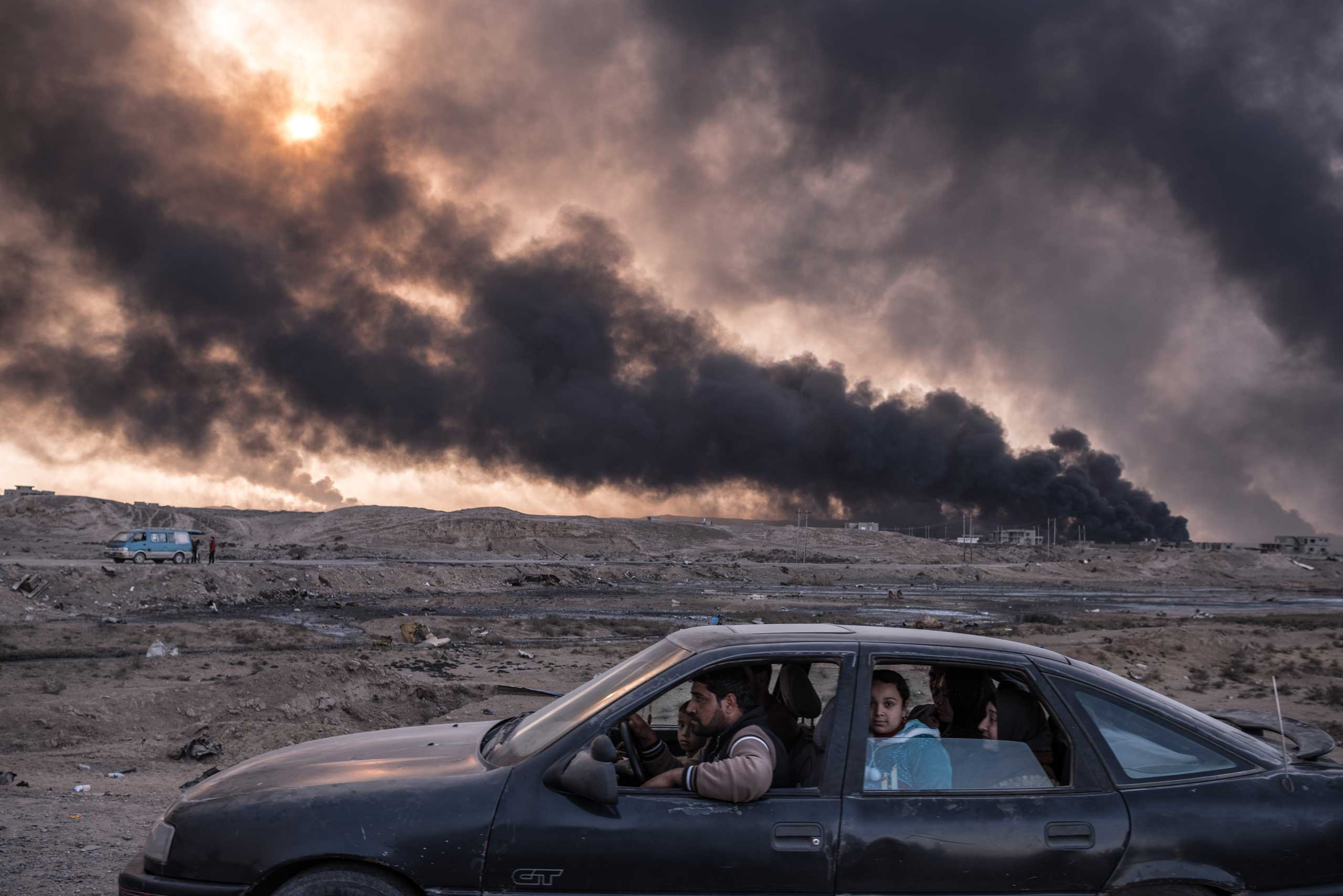 A family flees the fighting in Mosul, Iraq's second-largest city, as oil fields burned in Qayyara, Iraq, on Nov. 12, 2016.