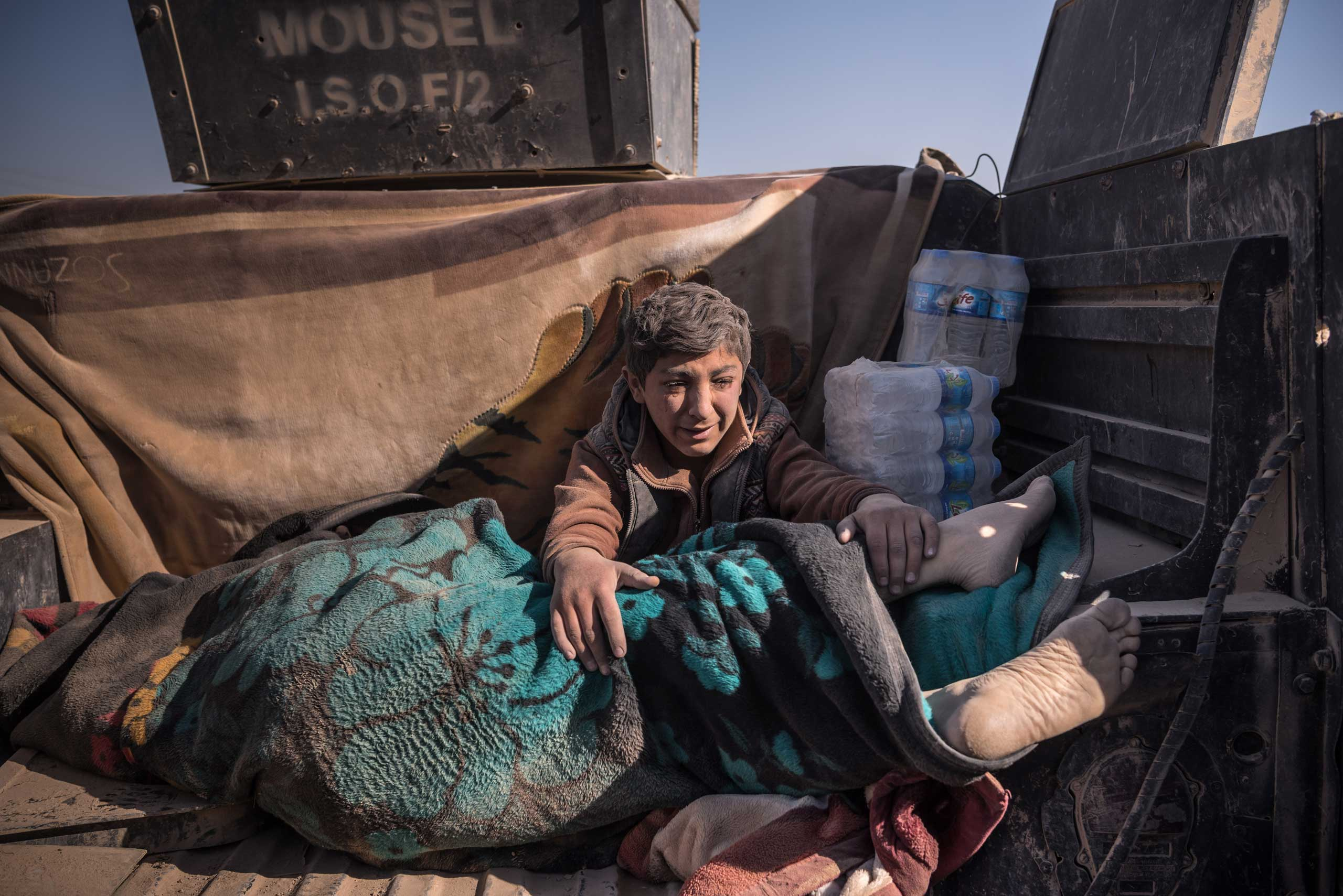 A boy holds the body of his father, killed by the Islamic State, as he arrived at a field hospital on the outskirts of Mosul, Iraq on Nov. 23, 2016.