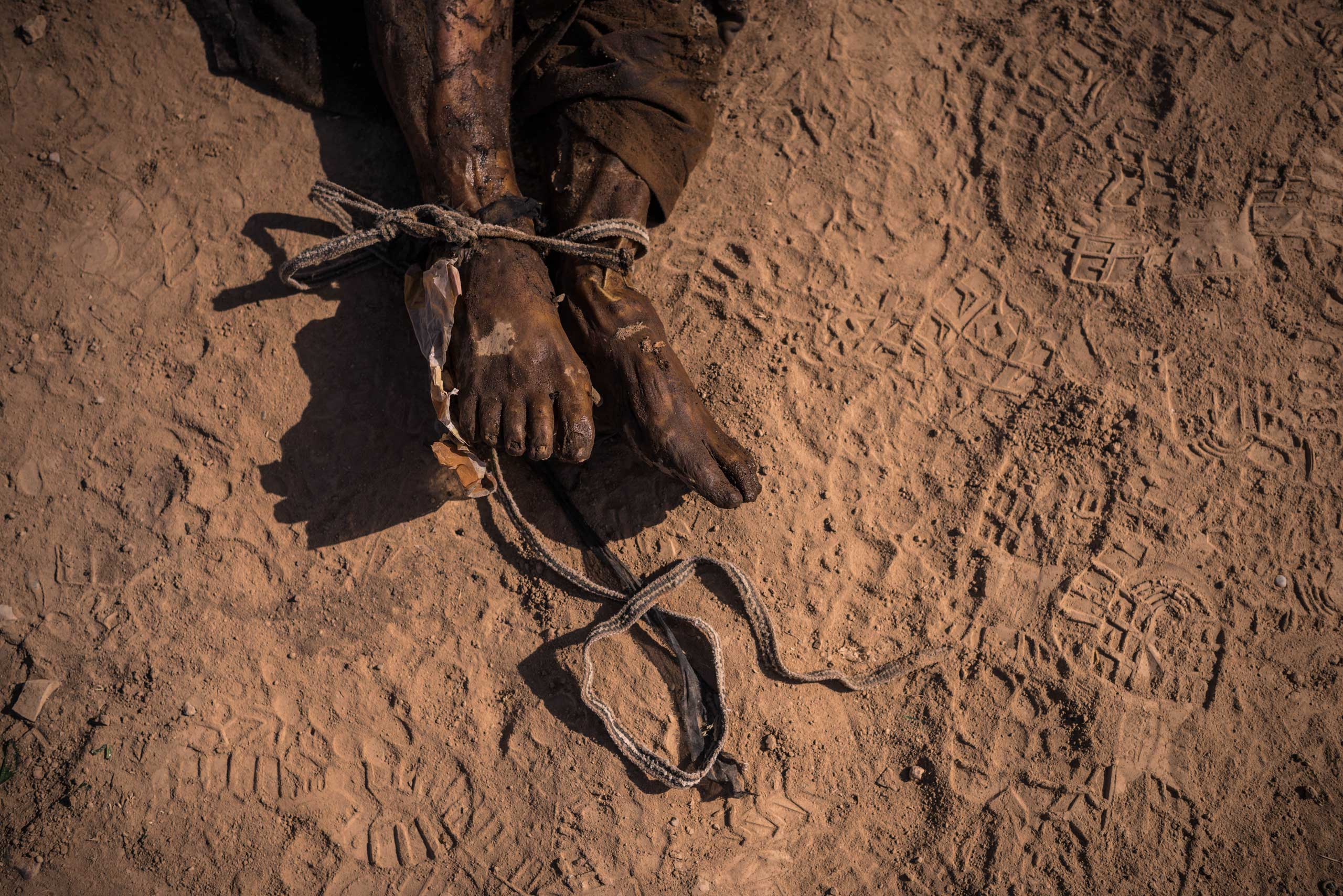 A tied, decomposed body is seen at the site of a mass grave that was discovered on the outskirts of Hamam al-Alil, Iraq on Nov. 12, 2016.