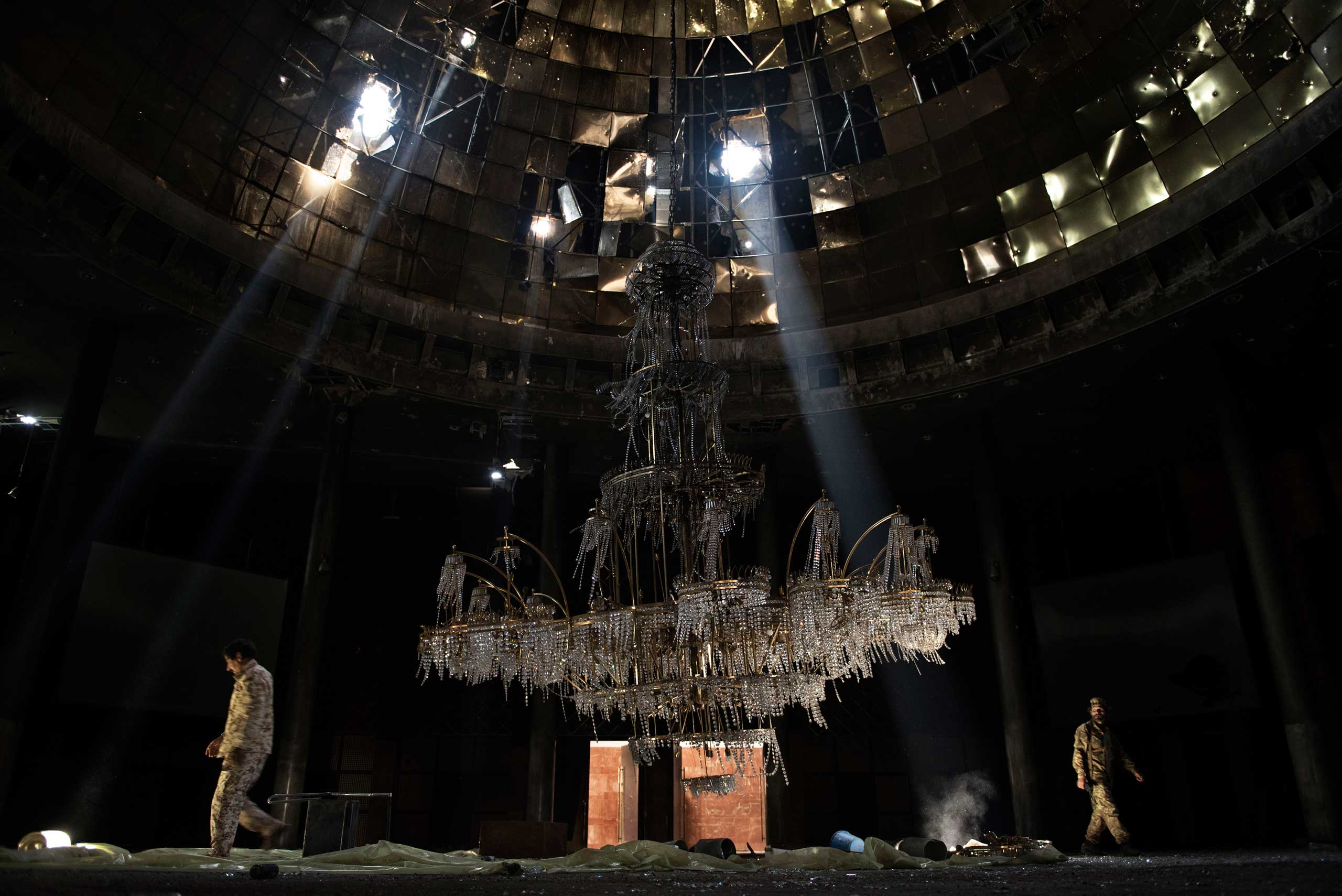 Fighters of the Libyan forces affiliated to the Tripoli government walk around the gigantic chandelier of the conference room in Ouagadougou congress complex on July 14, 2016.