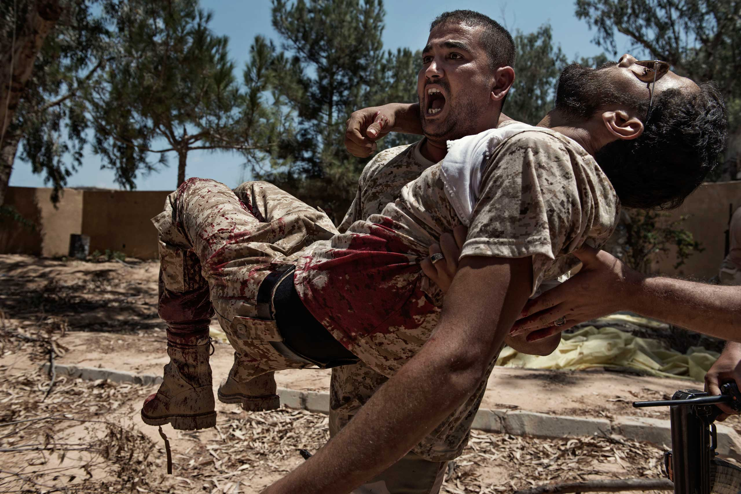 A fighter of the Libyan forces affiliated to the Tripoli government carries a comrade who was seriously injured just seconds before by a booby trap placed by ISIS fighters on July 14, 2016.
