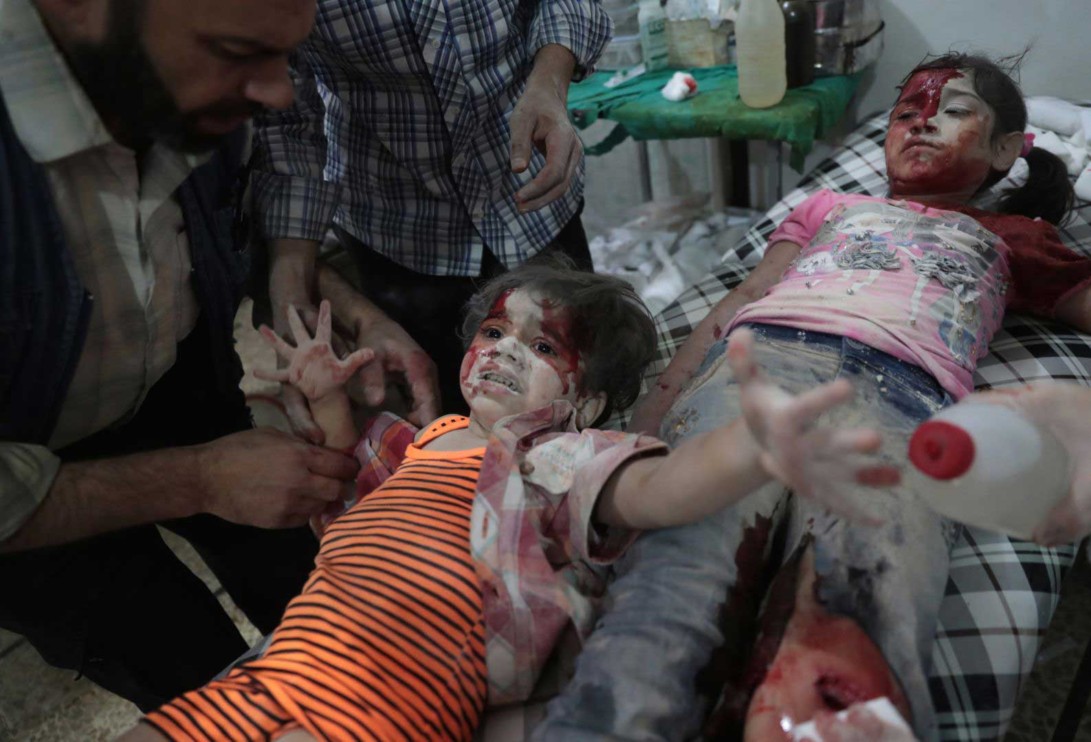 A Syrian girl cries out as a wounded child lies next to her at a makeshift hospital on Sept. 12, 2016. She had been injured in reported government airstrikes on the rebel-held town of Douma, east of Damascus, Syria.