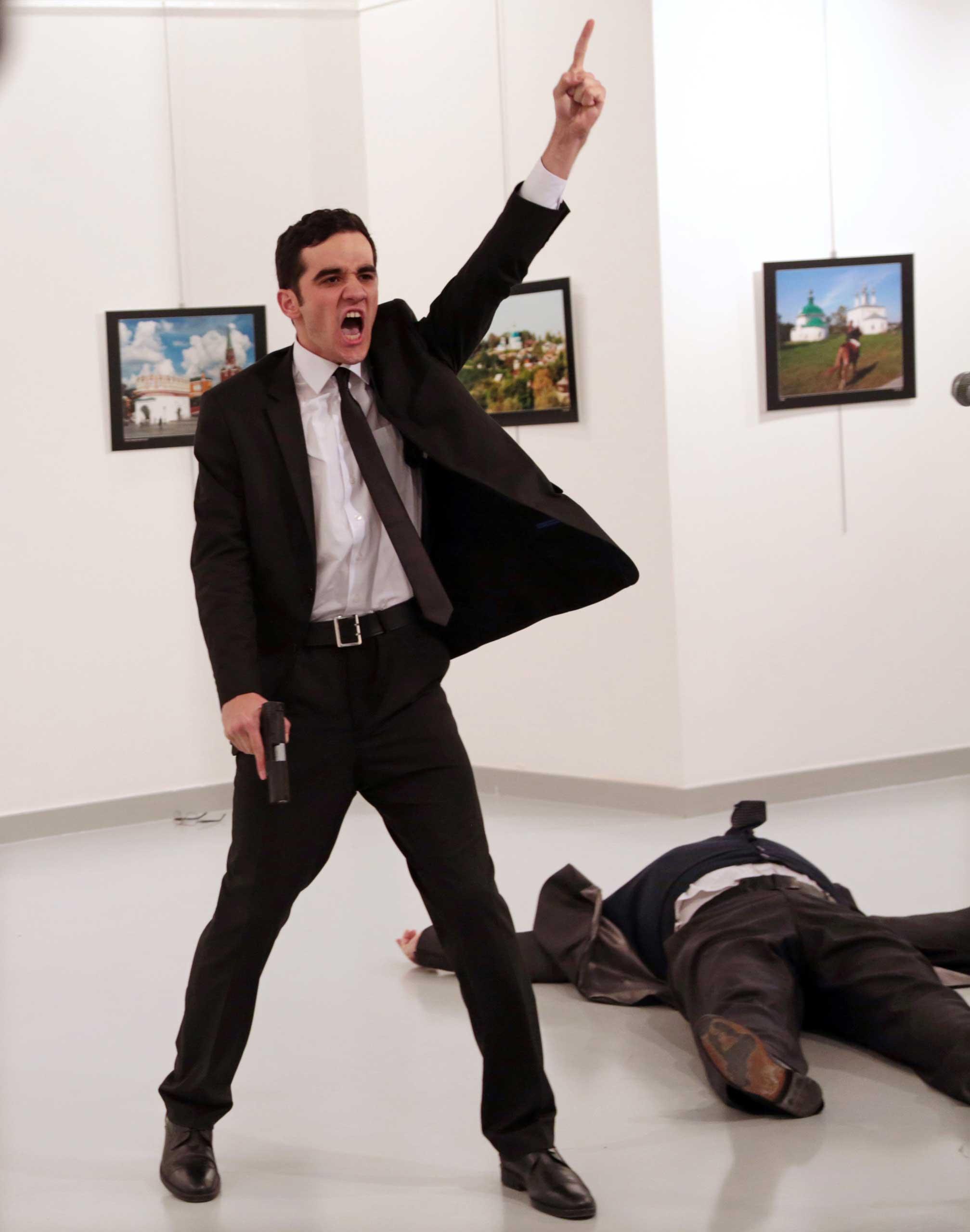 Mevlut Mert Altintas shouts after shooting Andrei Karlov, right, the Russian ambassador to Turkey, at an art gallery in Ankara, Turkey, Dec. 19, 2016.