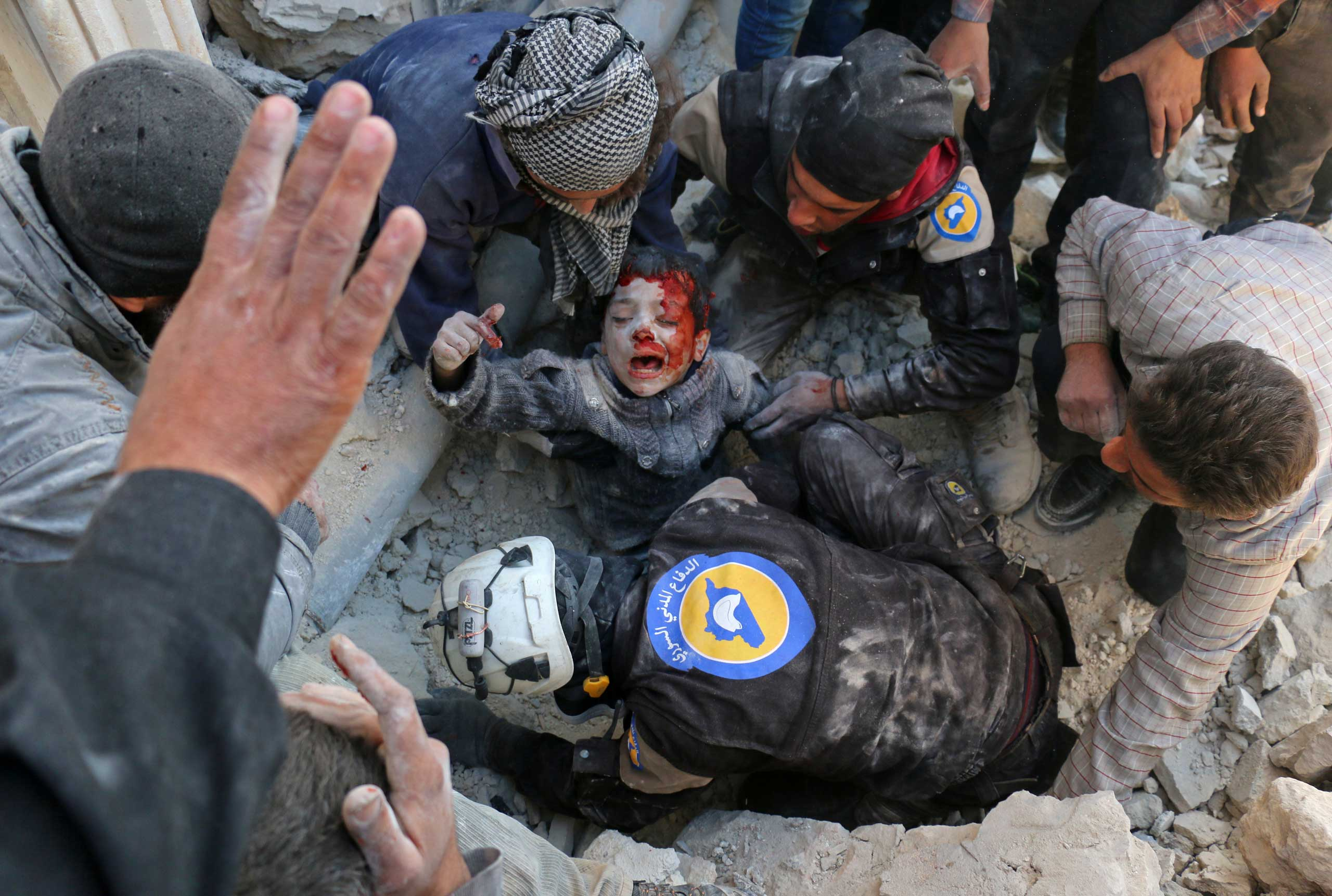 Syrian civil defence volunteers, known as the White Helmets, rescue a boy from the rubble following a reported barrel bomb attack on the Bab al-Nairab neighbourhood of the northern Syrian city of Aleppo on Nov. 24, 2016.