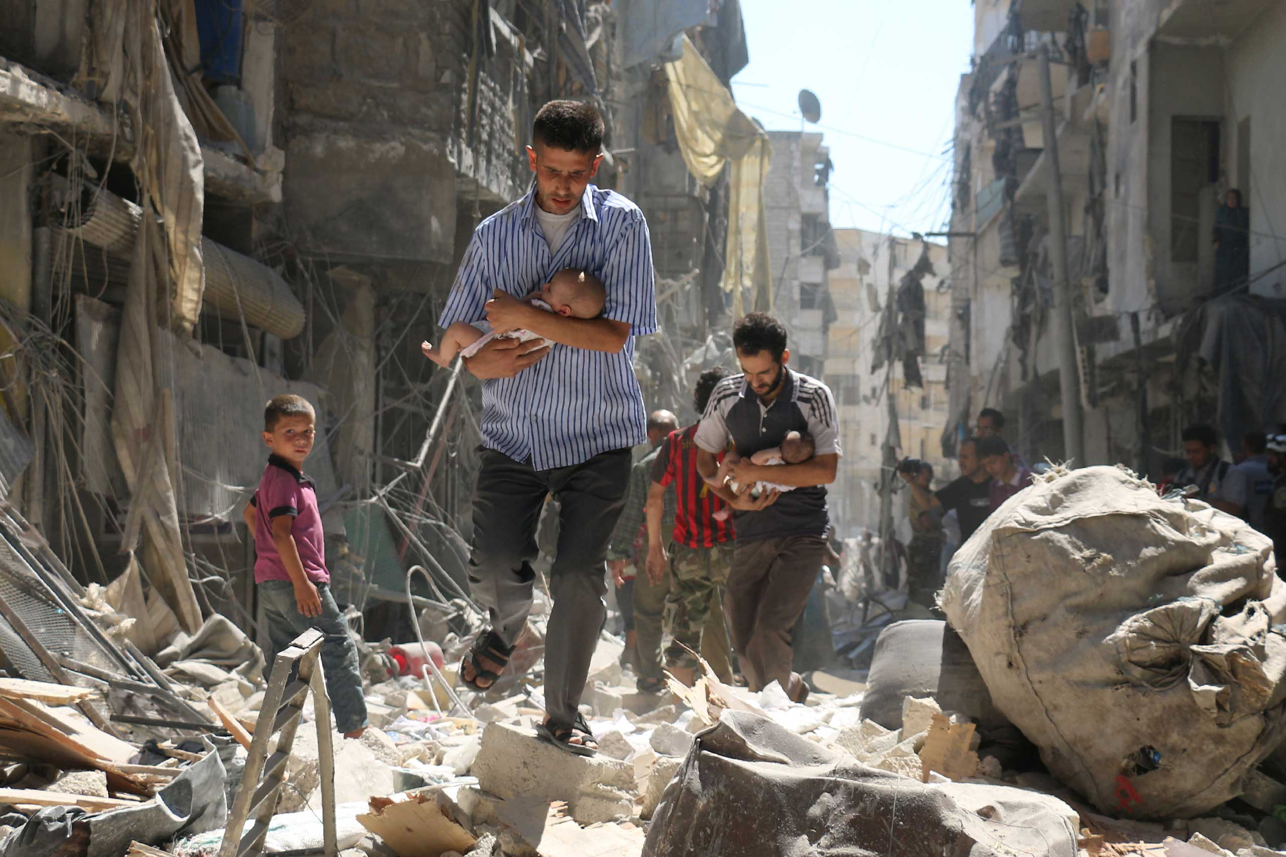 Syrian men carrying babies make their way through the rubble of destroyed buildings following a reported air strike on the rebel-held Salihin neighbourhood of the northern city of Aleppo, on Sept. 11, 2016.
