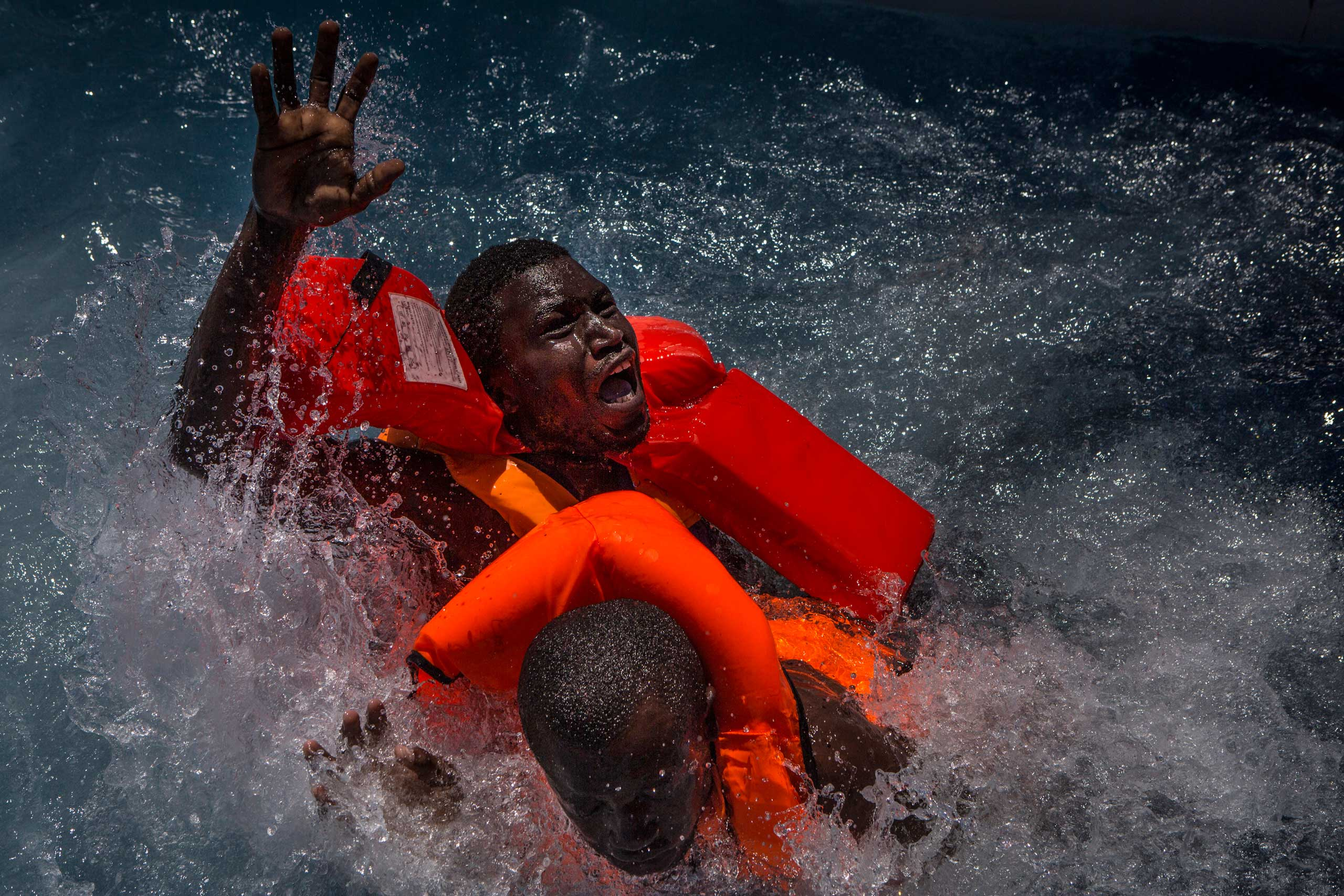 Two men panic and struggle in the water during their rescue. Their rubber boat was in distress and deflating quickly on one side, tipping many migrants in the water. They were quickly reached by rescue swimmers and brought to safety.