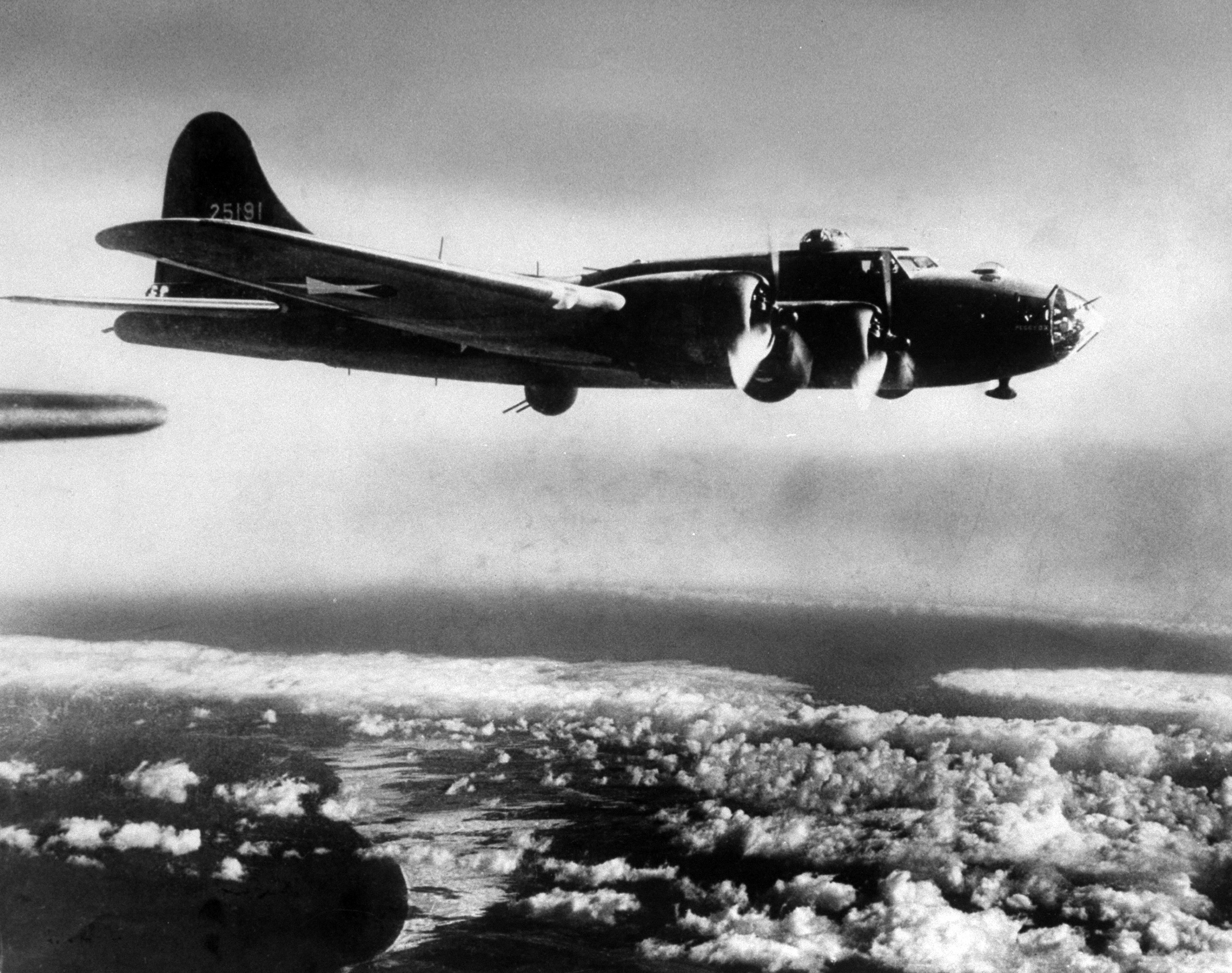 <b>Caption from LIFE.</b> Flying Fortress is photographed by Margaret Bourke-White as it heads east along cloud-banked Mediterranean coast to bomb Axis airport near Tunis.