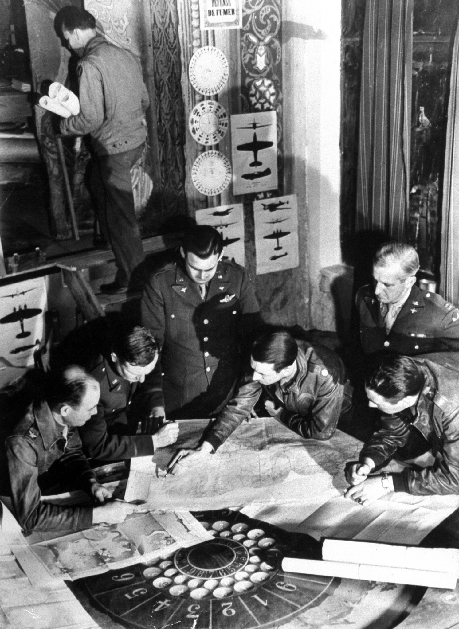 <b>Caption from LIFE.</b> Planning the mission at Bomber Wing Headquarters, operations and intelligence officers carefully study maps of the proposed target, El Auina airfield near Tunis. The gaming table on which the charts are spread belonged to occupents of pre-war days. Favorite gag of American combat crews based here is to suggest using dice to shoot for the target.