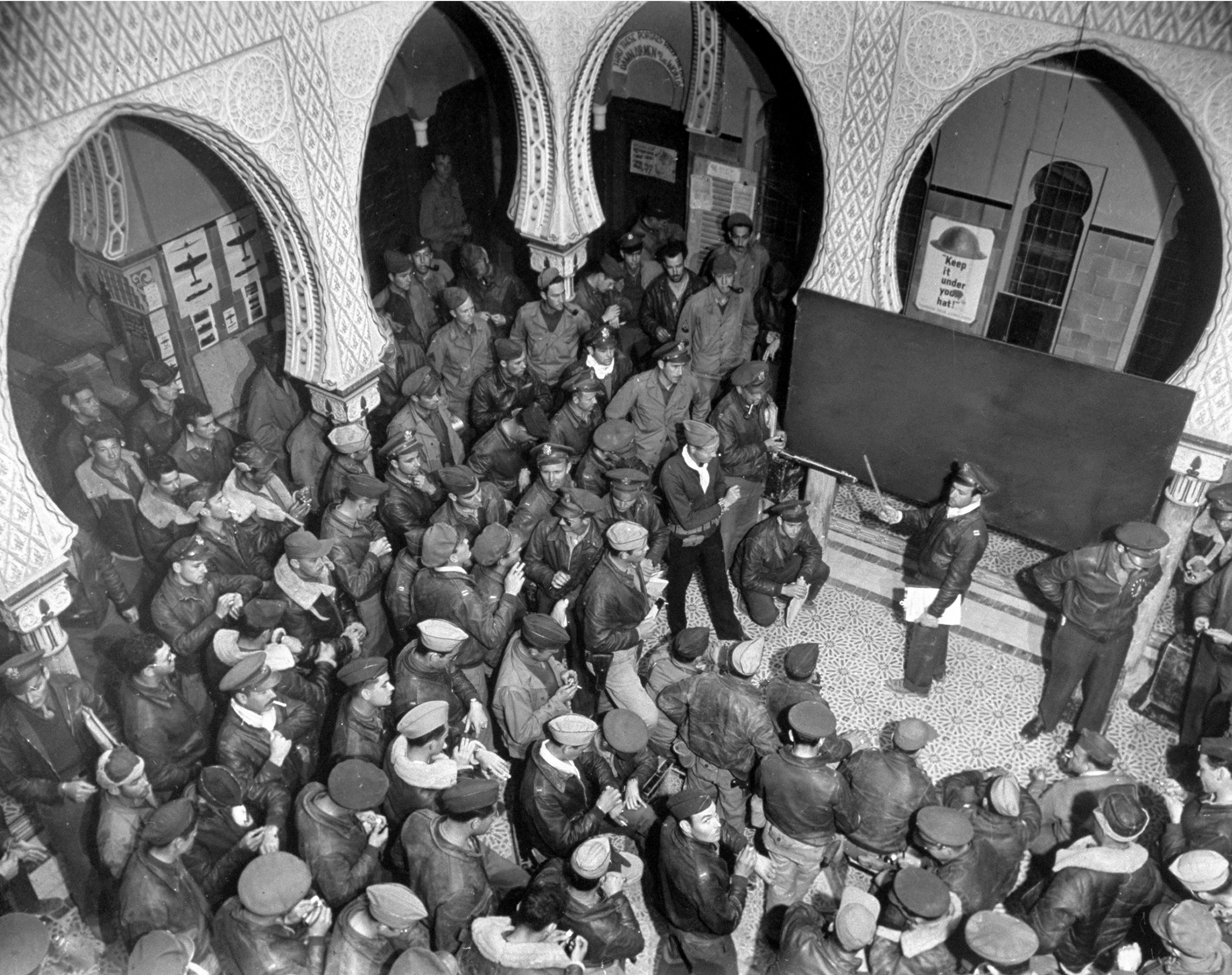 <b>Caption from LIFE.</b> Combat crew are briefed in the patio of an old desert palace now used by U.S. Air Force as an operations building. Scarcely an hour after the briefing, pilots and crews were in the air, Tunis-bound.