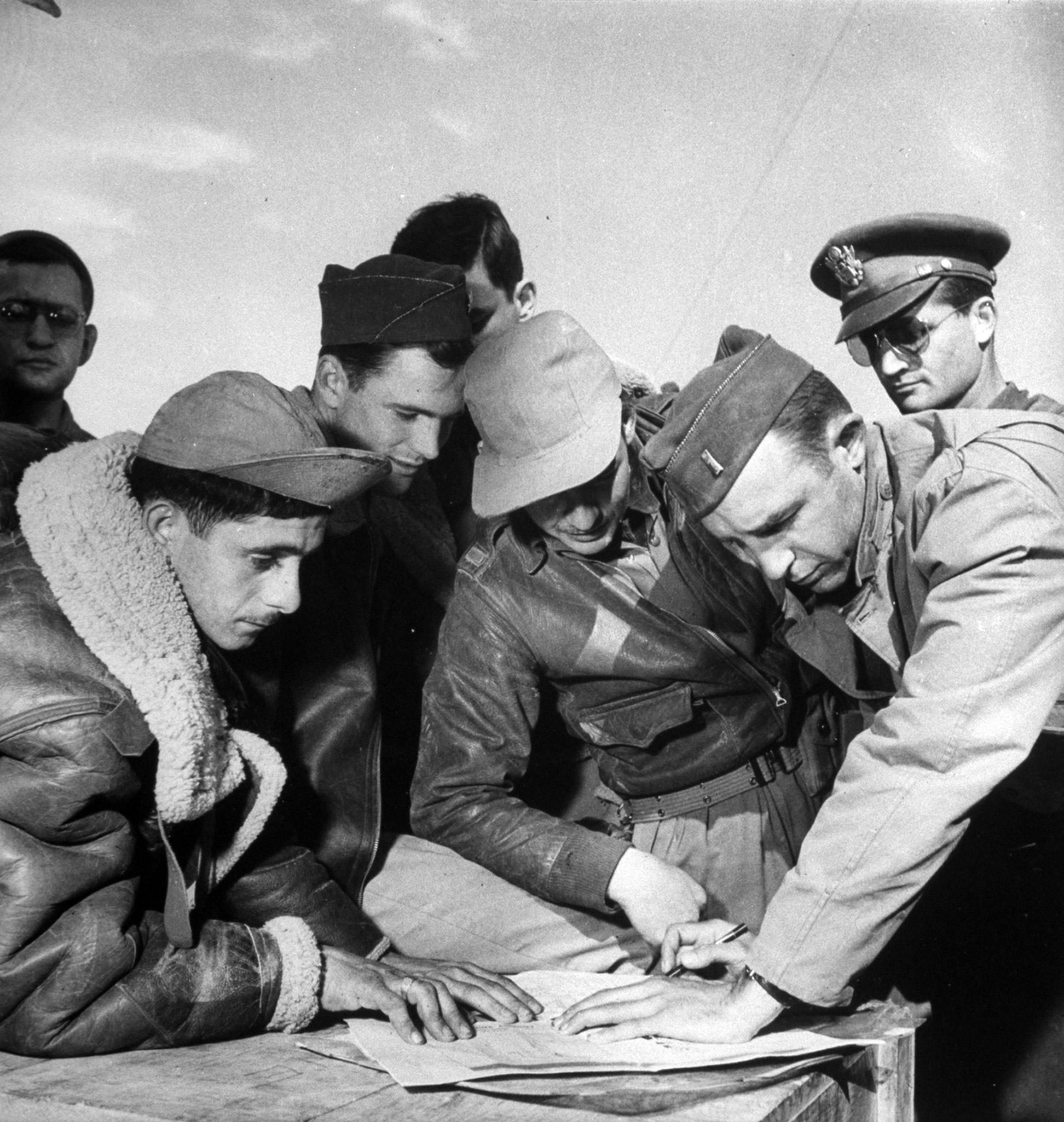 B17 bomber crew sharing bombing raid details of target in Tunis in North Africa with intelligence officers, during WWII.