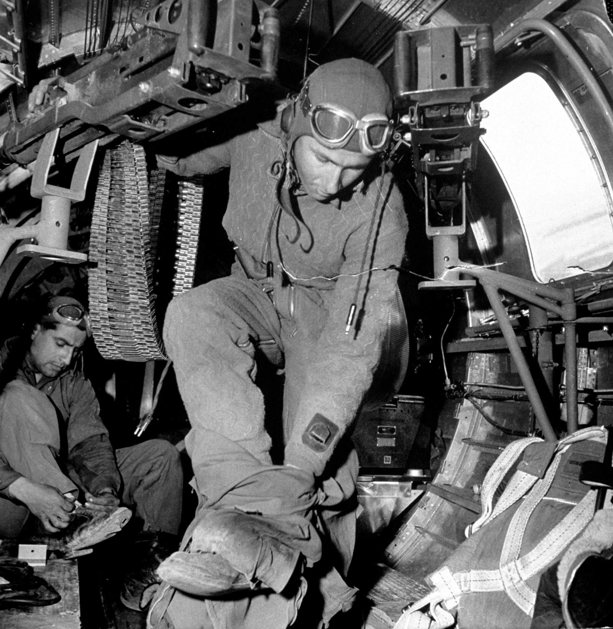 """Ball turret gunner Sgt. James M. Abbott, holding onto one of the 50-cal. waist machine guns as he takes off his warm high altitude clothing upon return from a successful bombing mission in the Amer. B-17 """"Little Bill"""", at Sahara desert airdrome."""