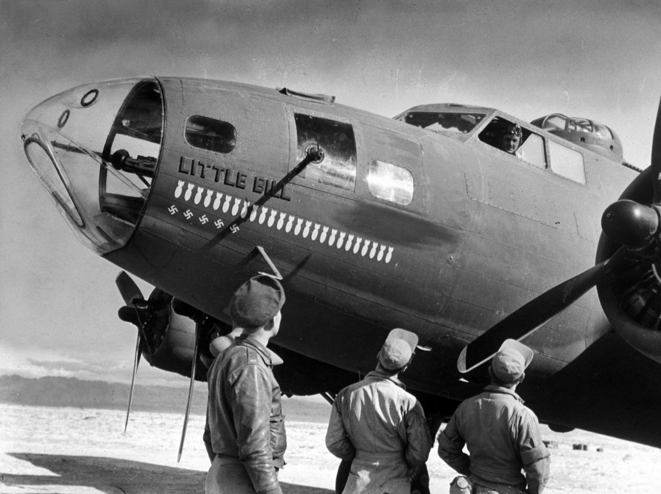 """<b>Caption from LIFE.</b> """"Little Bill"""" lead plane of lead element, prepares to take off. Bombs painted on nose denote a mission in which it participated; swastikas, number of German planes shot down."""