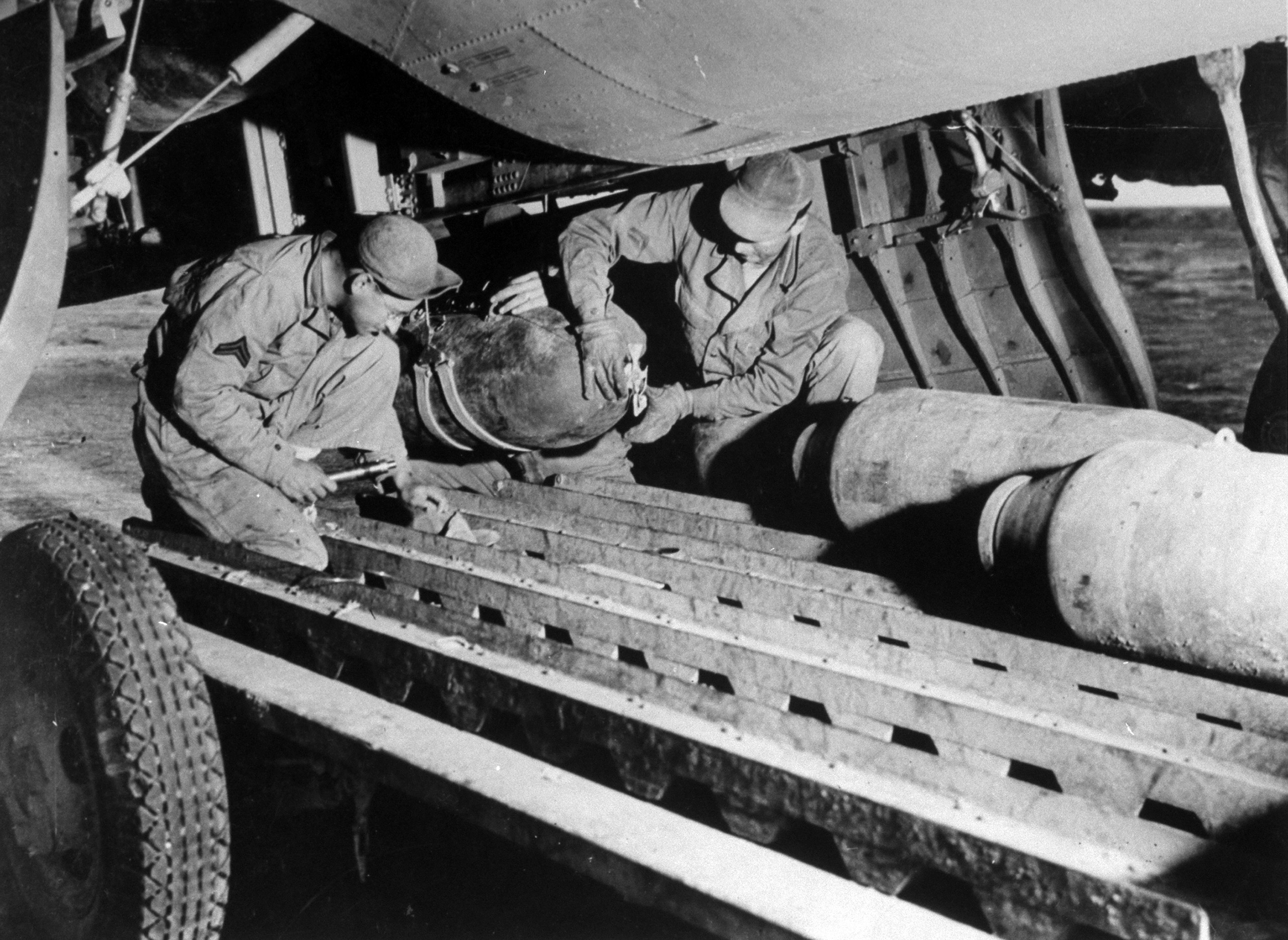 """<b>Caption from LIFE.</b> Ground crew, """"bombs up' a Fortress. In this raid mostly fragmentation bombs were used in order to spray the planes to best advantage. Here amorers are placing bombs in a sling to hoist on racks."""