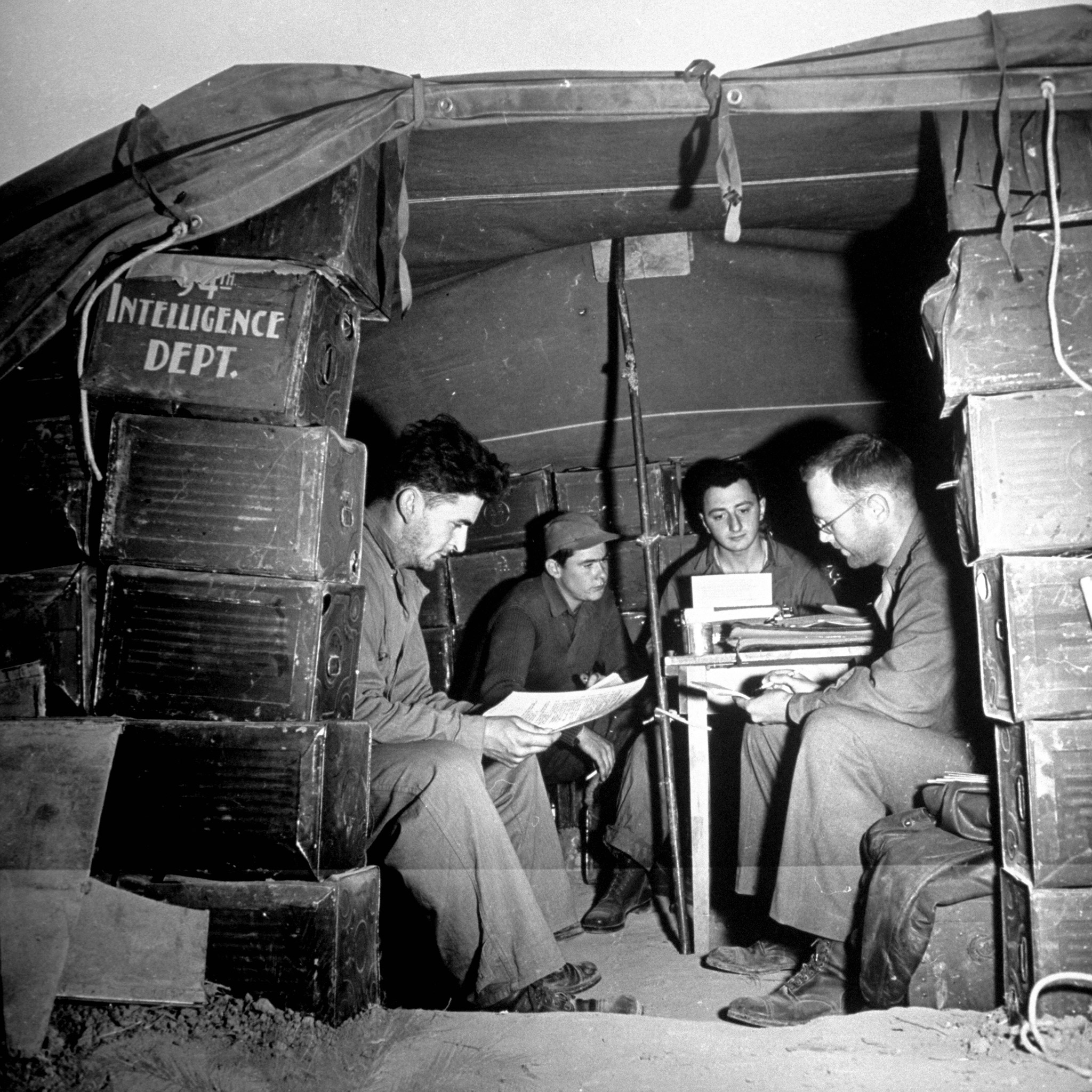 Men of the Intelligence dept. of the 94th Fighter Group gathered around man at typewriter who is typing up combat reports on the last bombing mission in which their group escorted B-17s, at airdrome in the Sahara.