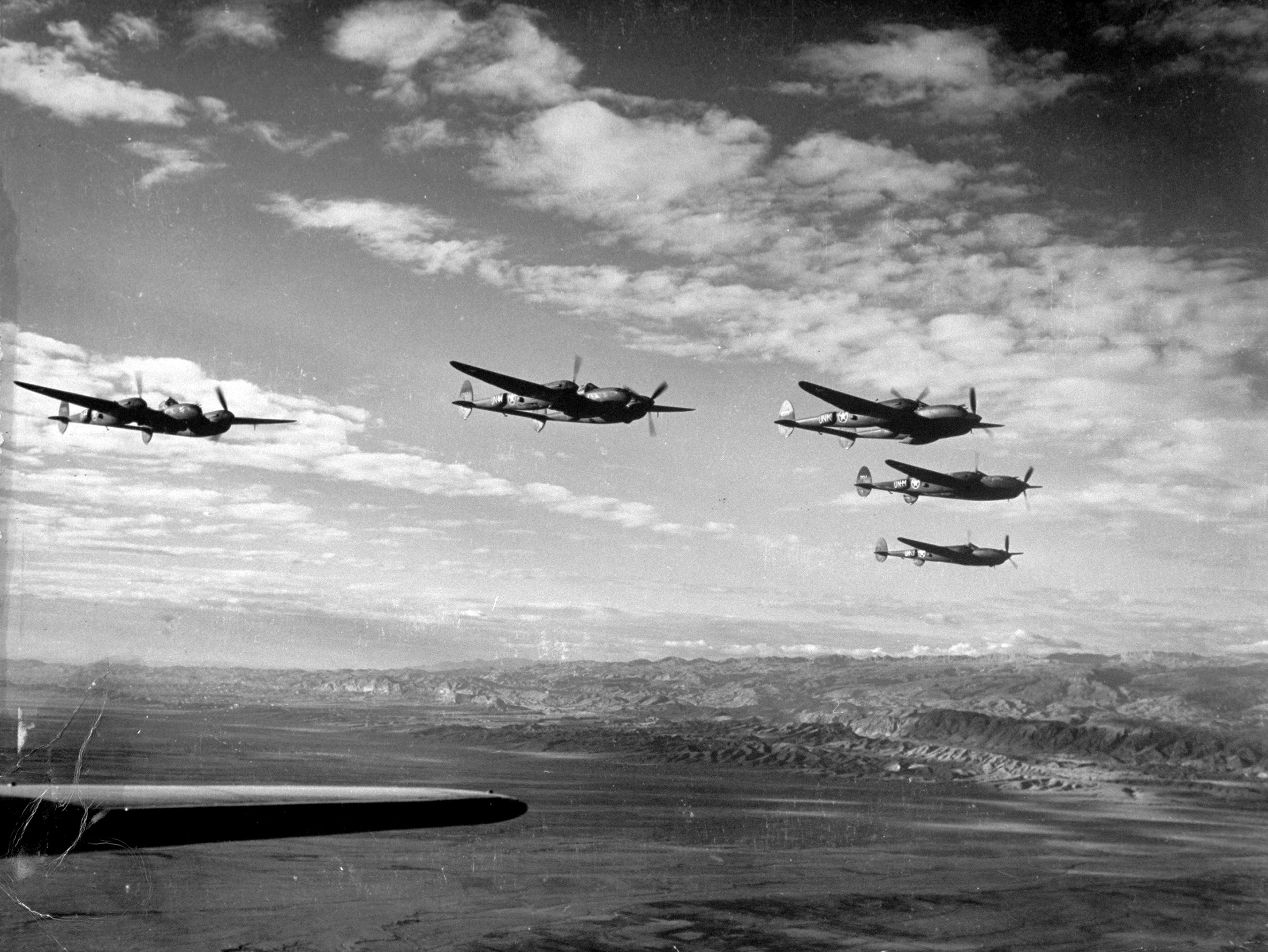 Protective screen of five American P-38 fighter planes over the arid Atlas mountains, viewed from over tail of an American medium bomber which they are escorting during its bombing mission to its target at El Aliuna airbase in Tunis.