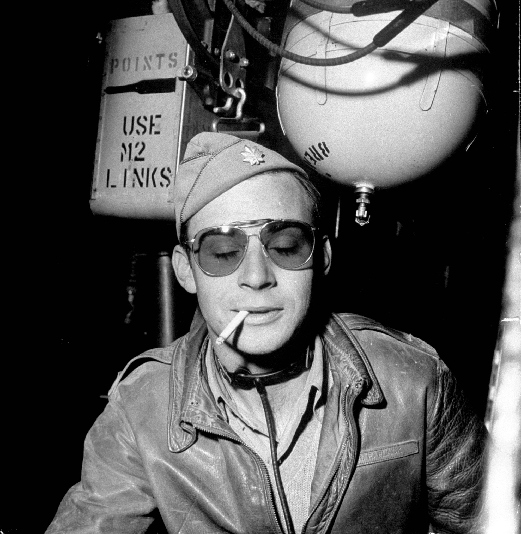 """Major  Rudolph Flack, Squadron Commander/Pilot of B-17 Flying Fortress """"Little Bill"""" relaxing with a cigarette inside his plane after returning from successful bombing mission in Tunisia, at Sahara desert airdrome."""