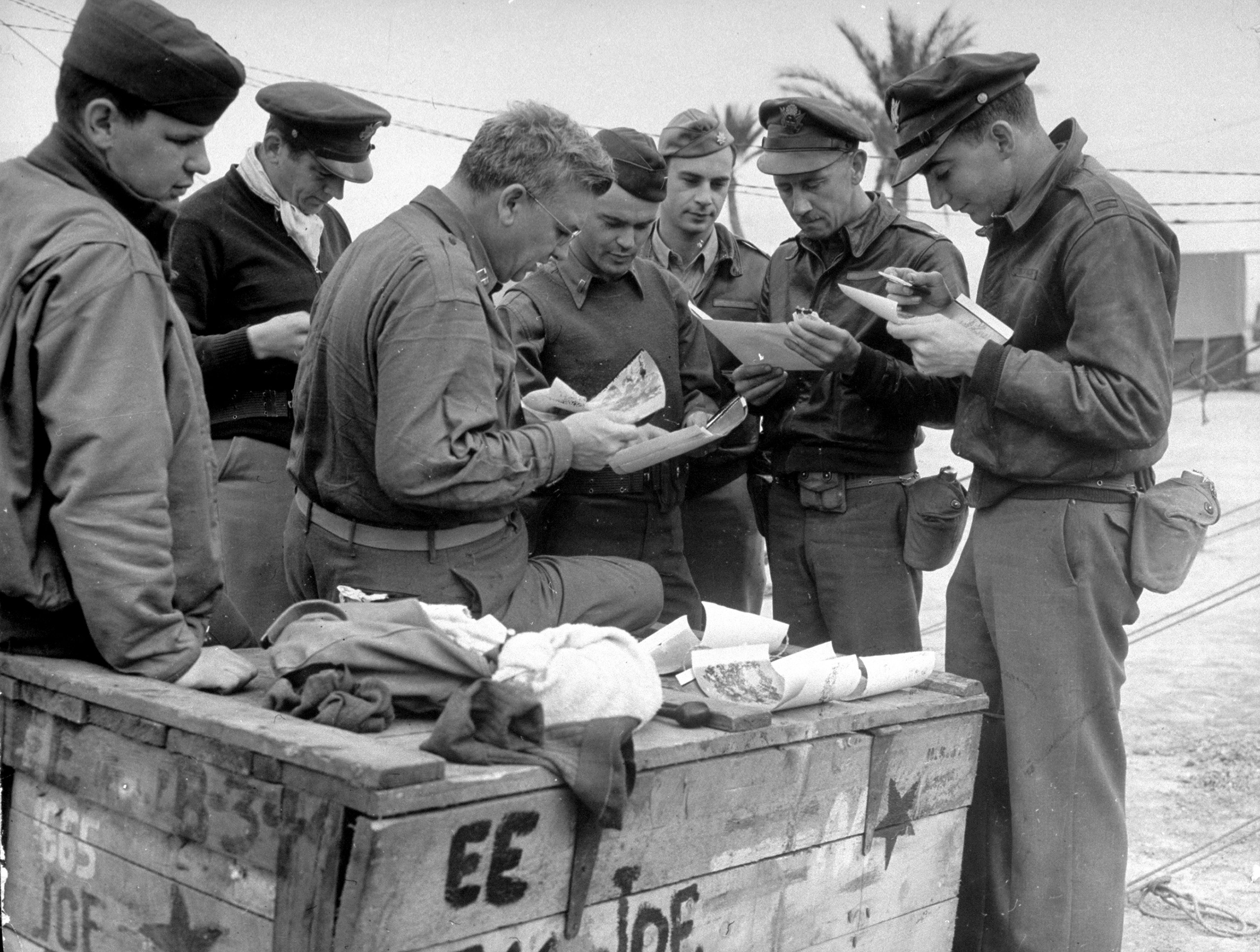 12th Air Force intelligence group officer Capt. Hazen Payette (3L) examing photographs of bombing raid with B-17 officers and crewmen including Lt. Carl Schultz (2L), Lt. Ed Weathers, Maj. Rudolph Flack, Maj. Joe Thomas (2R), at desert base during Allied North African campaign, WWII.