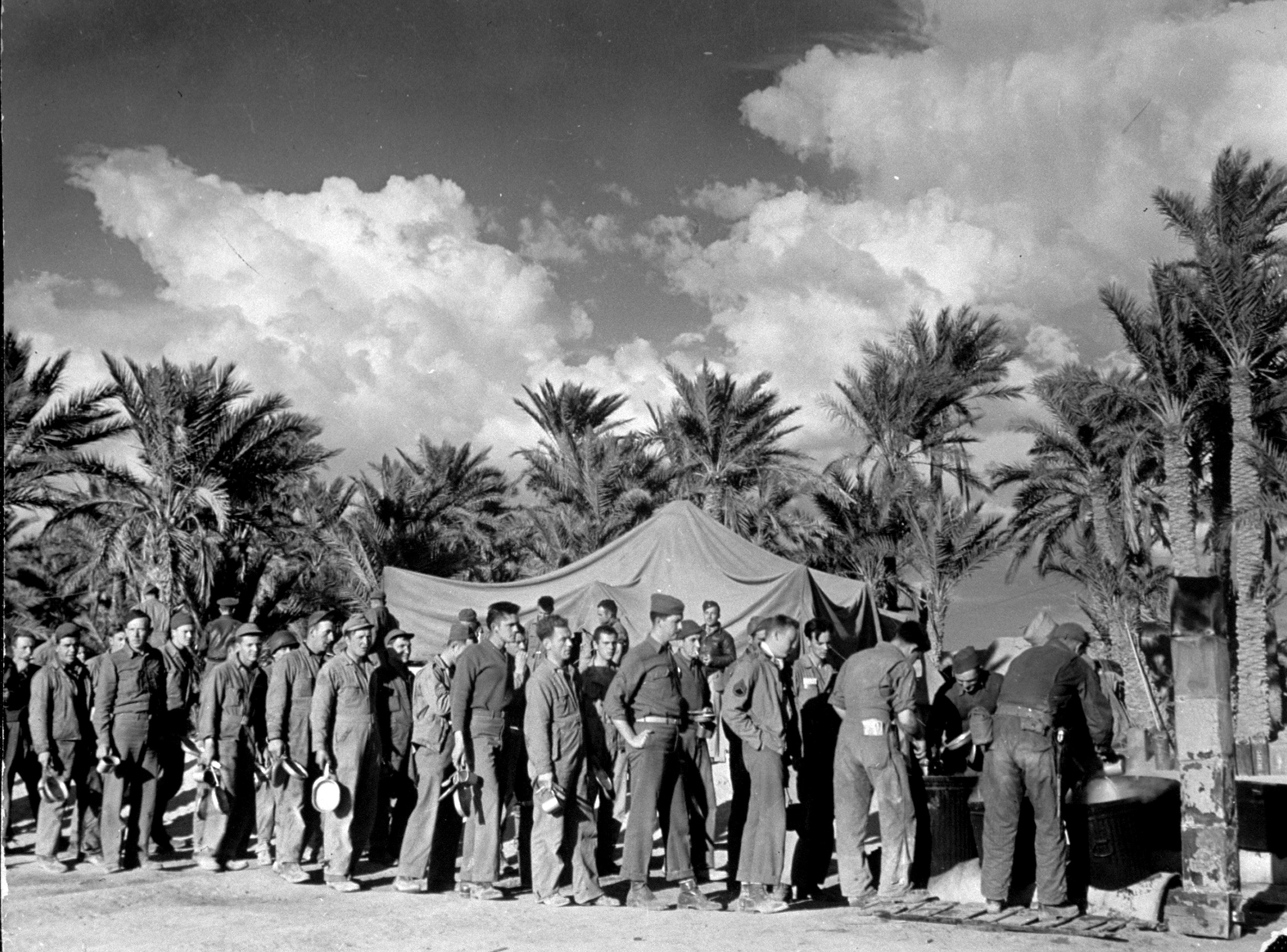 U.S. 12th Air Force ground crew and pilots after completing bombing mission, lined up with their mess kits, waiting to get food from large cooking pots at the right of the line, outside mess tent at their Sahara desert airdrome.
