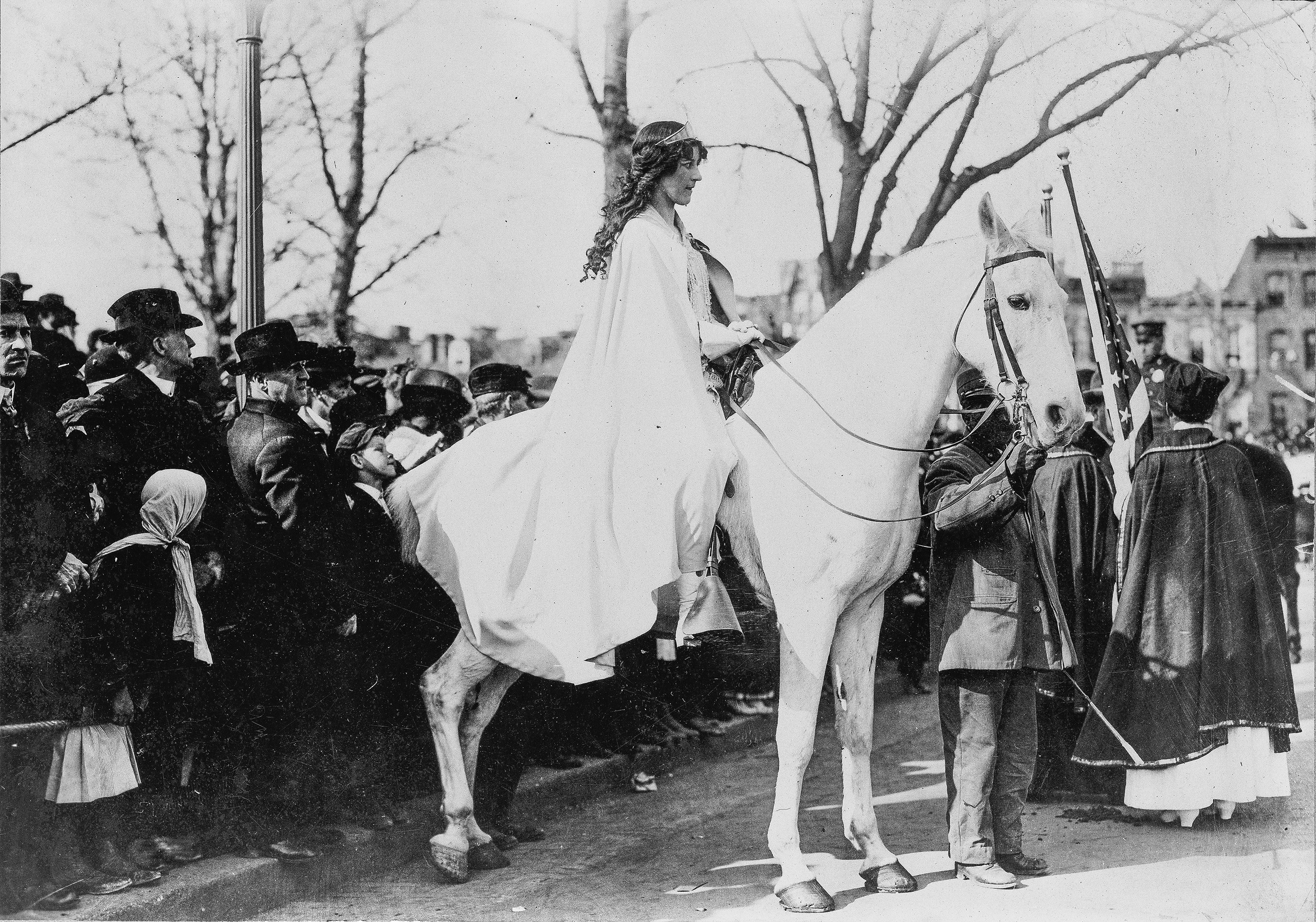 Inez Milholland Boissevain, wearing a white cape, seated on a white horse at the National American Woman Suffrage Association parade.