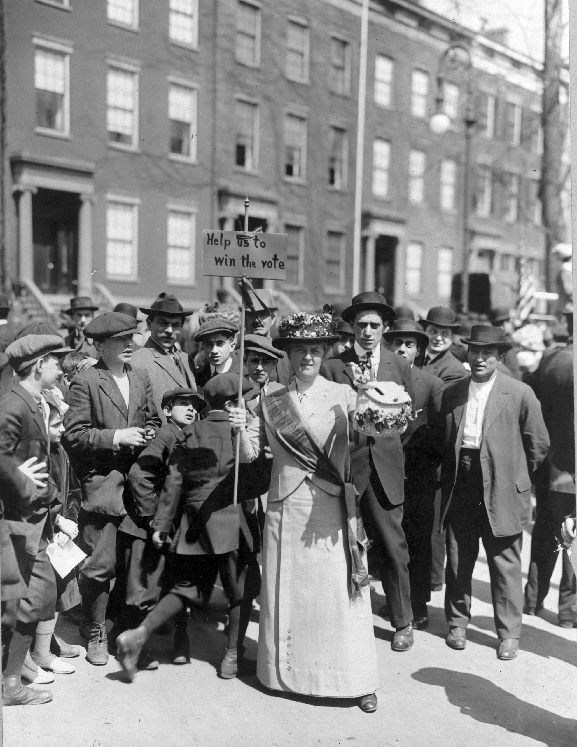 Mrs. Suffern wearing a sash and carrying a sign that says  Help us to win the vote,  surrounded by a crowd of men and boys at a Women's Suffrage Parade in 1914.