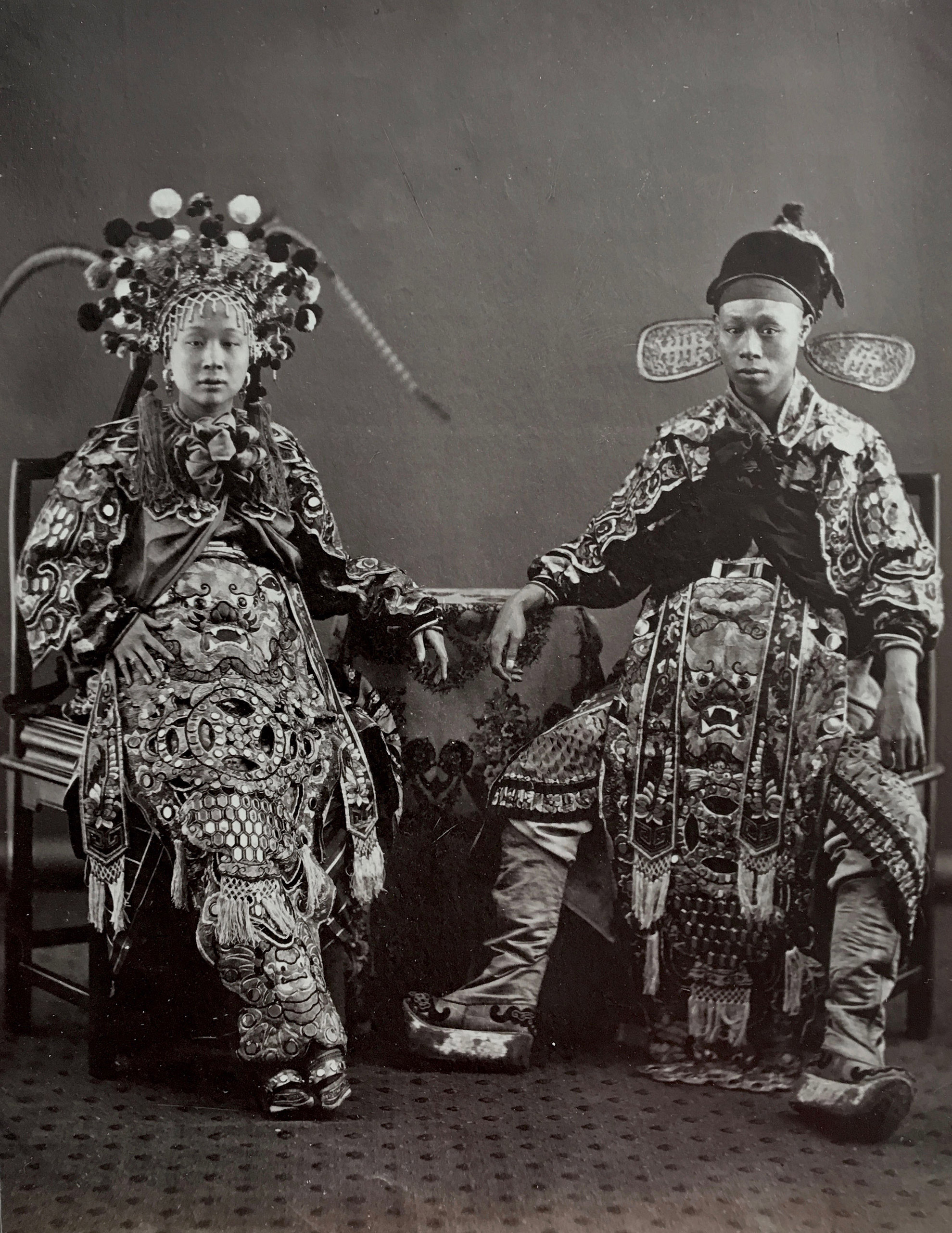 Caption from Stephan Lowentheil Collection. This striking portrait shows a Chinese actress and an actor in elaborate costumes. The costumes of Chinese theatre recalled much earlier, classical clothing made of lavishly embroidered, rich silks. Those playing villains often wore grotesque masks.