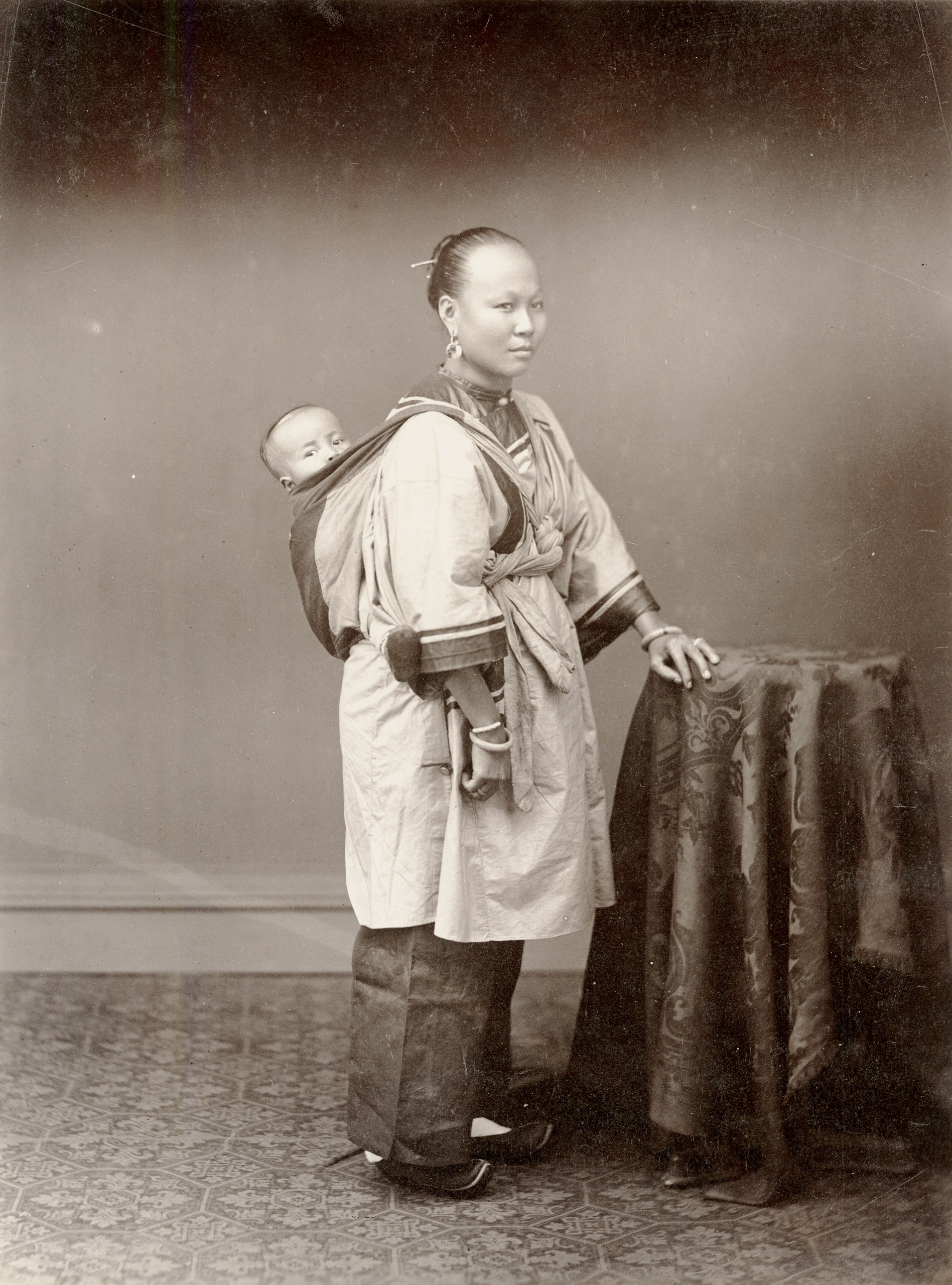Caption from Stephan Lowentheil Collection. Portrait of a woman carrying a child on her back. Though Pun Lun operated a large and successful studio, most of the photographs attributed to the artist are small carte de visite portraits. This large-format masterpiece from Pun Lun's genre series is a rare survival.