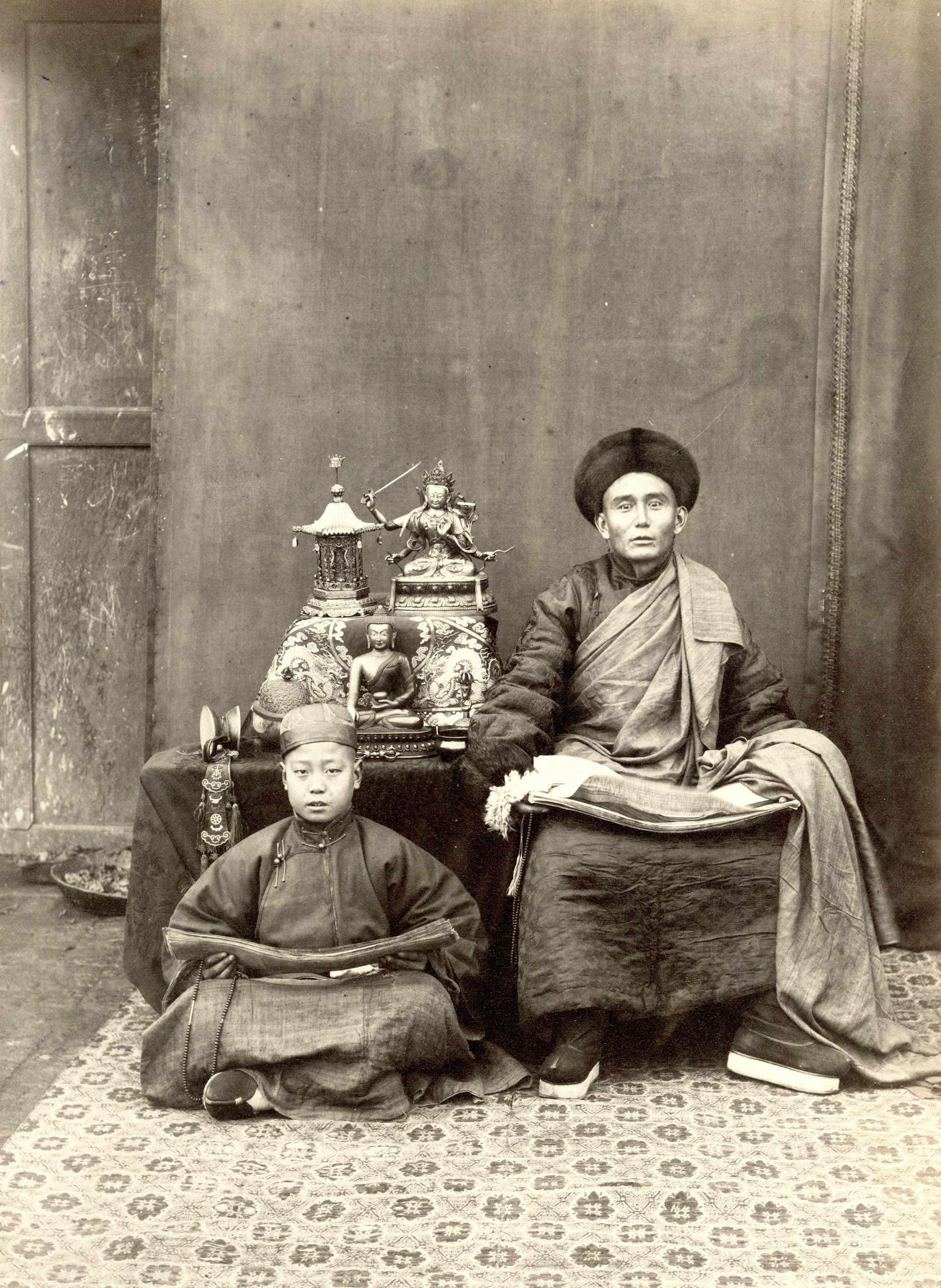 Caption from Stephan Lowentheil Collection. One of the earliest photographs of a religious figure in Peking. In the nineteenth century, the term 'lama' referred to any Tibetan Buddhist monk or teacher. The lama and his pupil both hold prayer beads and bundles of sutras in their laps. Displayed on the table are bronze sculptures and sacred Tibetan ritual objects including a cup made out of a human skull and a statue of Manjusri, bodhisattva of wisdom. One of the earliest photographs of such sacred objects, this image provides a valuable record of religious practice in the late Qing Dynasty.
