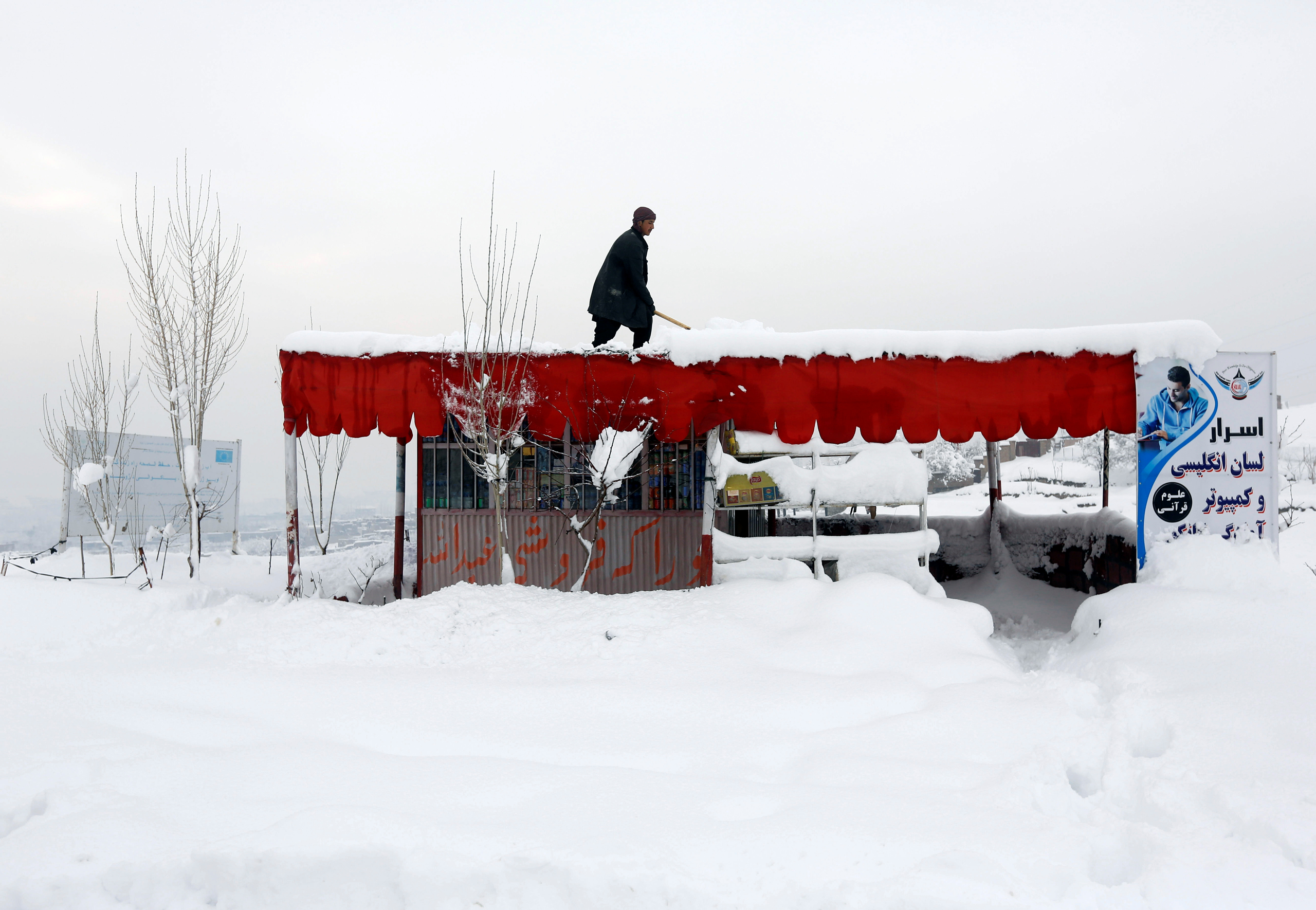 An Afghan man removes snow from his shop on the outskirts of Kabul on Feb. 5, 2017.