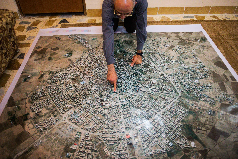 Father Georges kneels on a map of Qaraqosh.