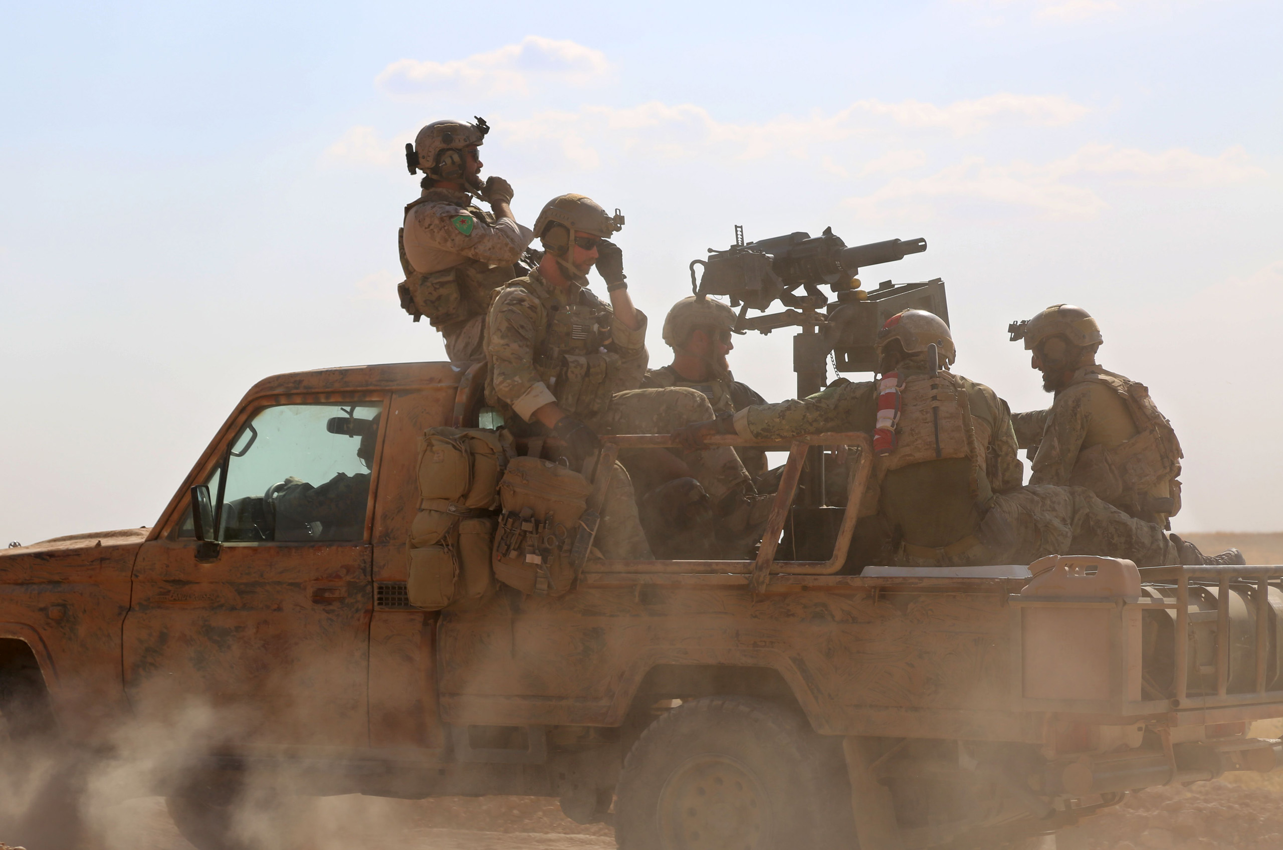 US special operations forces ride in the back of a pickup truck in the village of Fatisah in the northern Syrian province of Raqa on May 25, 2016.