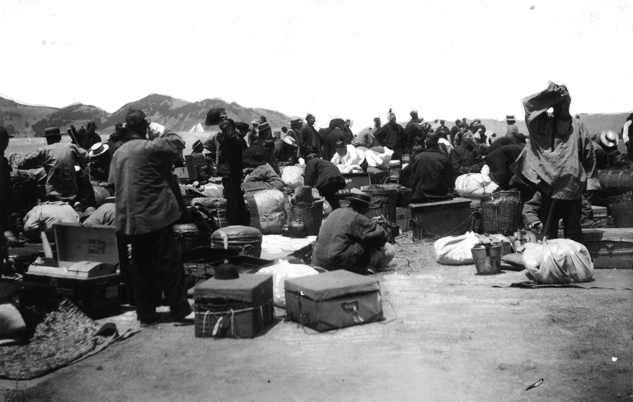 A group of  Chinese and East Asian immigrants wait on a wharf after disinfection at Angel Island, San Francisco Bay, California, ca. 1910s.