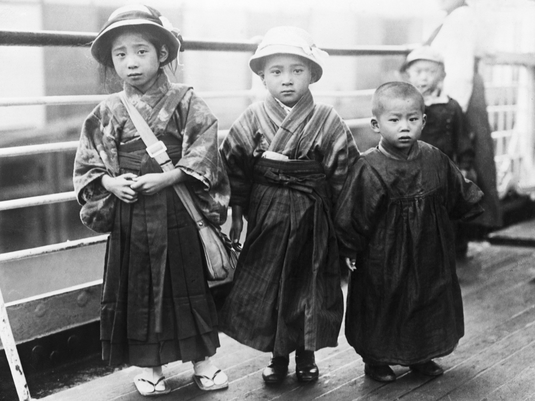 Three Japanese children stand on the deck of the Shinyo Maru as it arrives in San Francisco, ca. 1920.