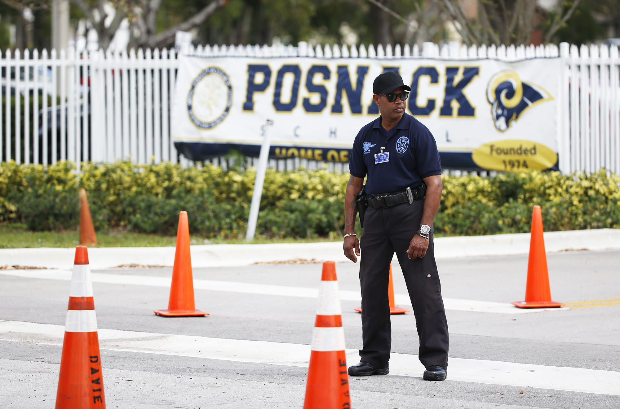 A security guard stands outside the entrance to the David Posnack Jewish Community Center and David Posnack Jewish Day School after people were evacuated because of a bomb threat, on Feb. 27, 2017, in Davie, Fla.