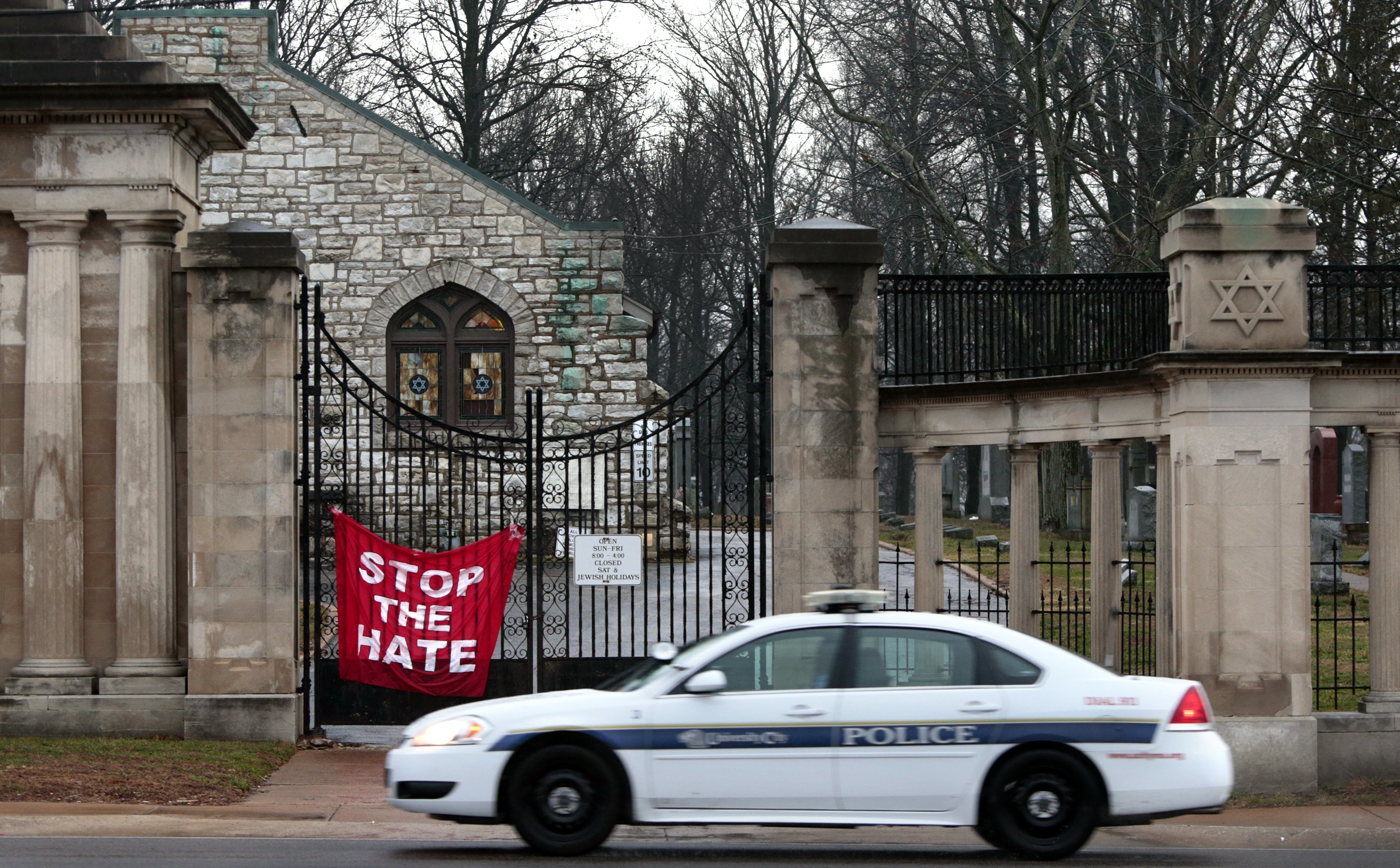 A University City police car patrols in front of Chesed Shel Emeth Cemetery in University City, Mo., on Feb. 21, 2017, following vandalism there. Separately, Jewish Community Centers across the country have recently been the target of bomb threats.