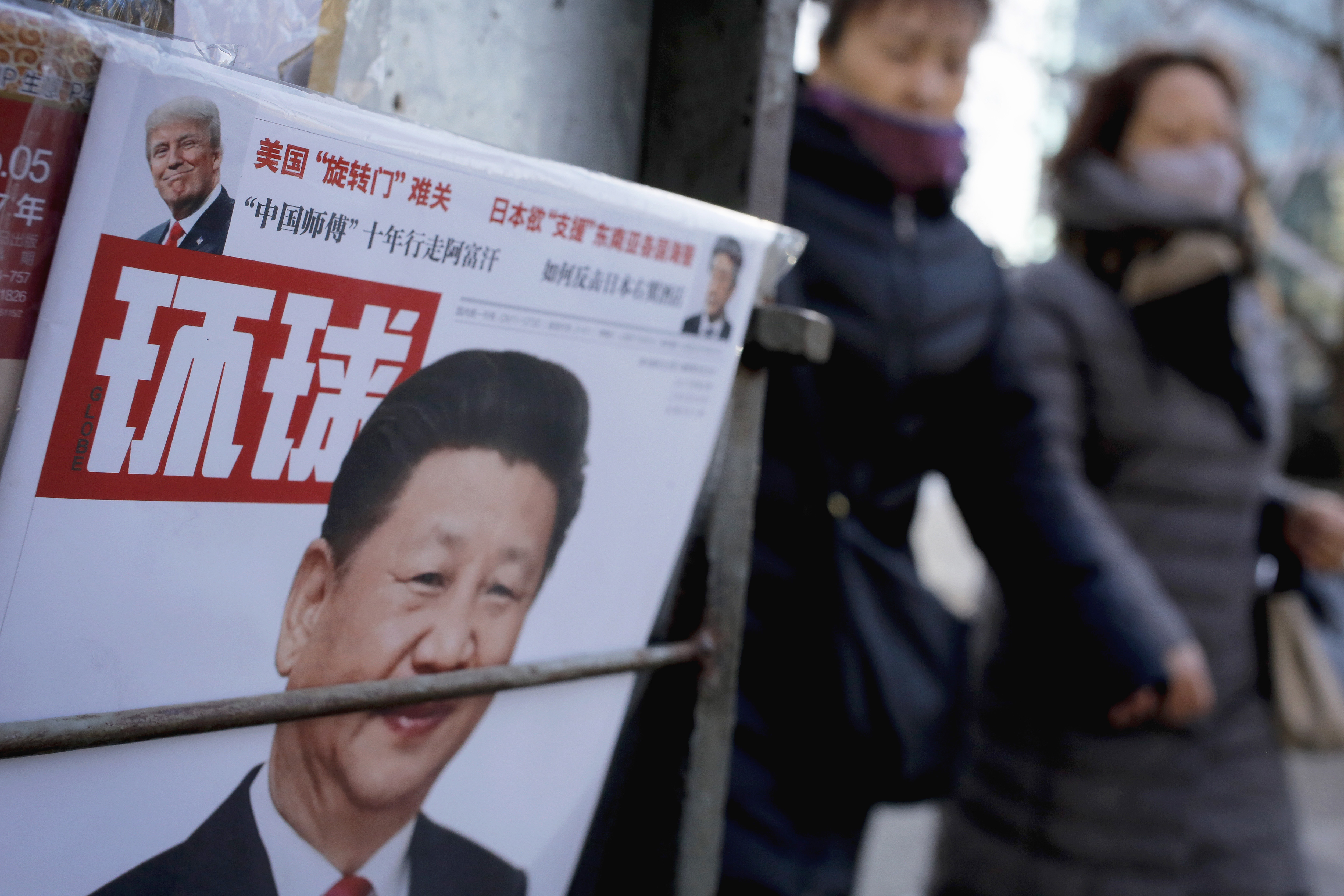 Women walk past a newsstand displaying a Chinese news magazine fronting a photo of Chinese President Xi Jinping and that of U.S. President Donald Trump in Beijing on Feb. 9, 2017