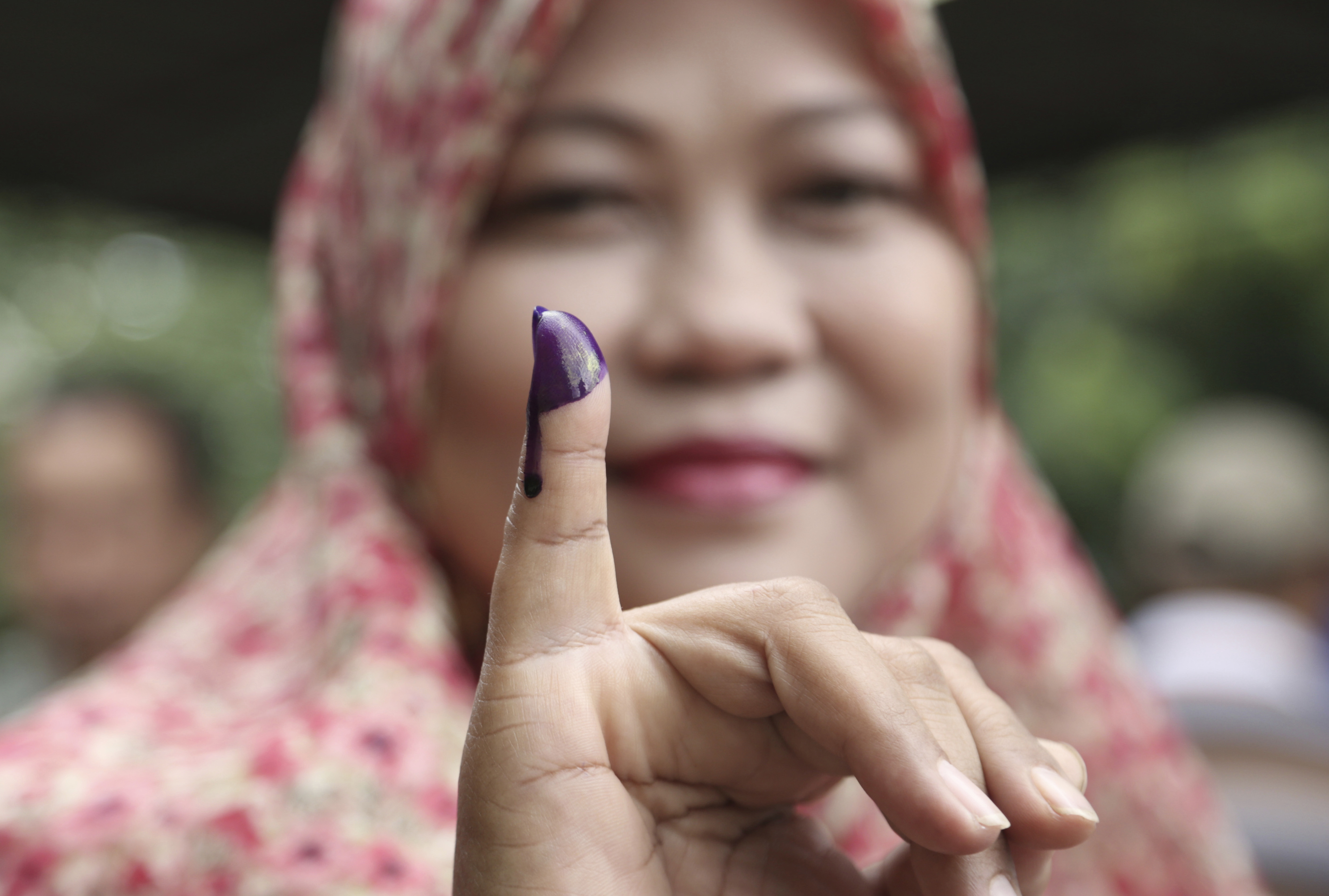 A Muslim woman shows her ink-stained finger after voting in the gubernatorial election in Jakarta on Feb. 15, 2017