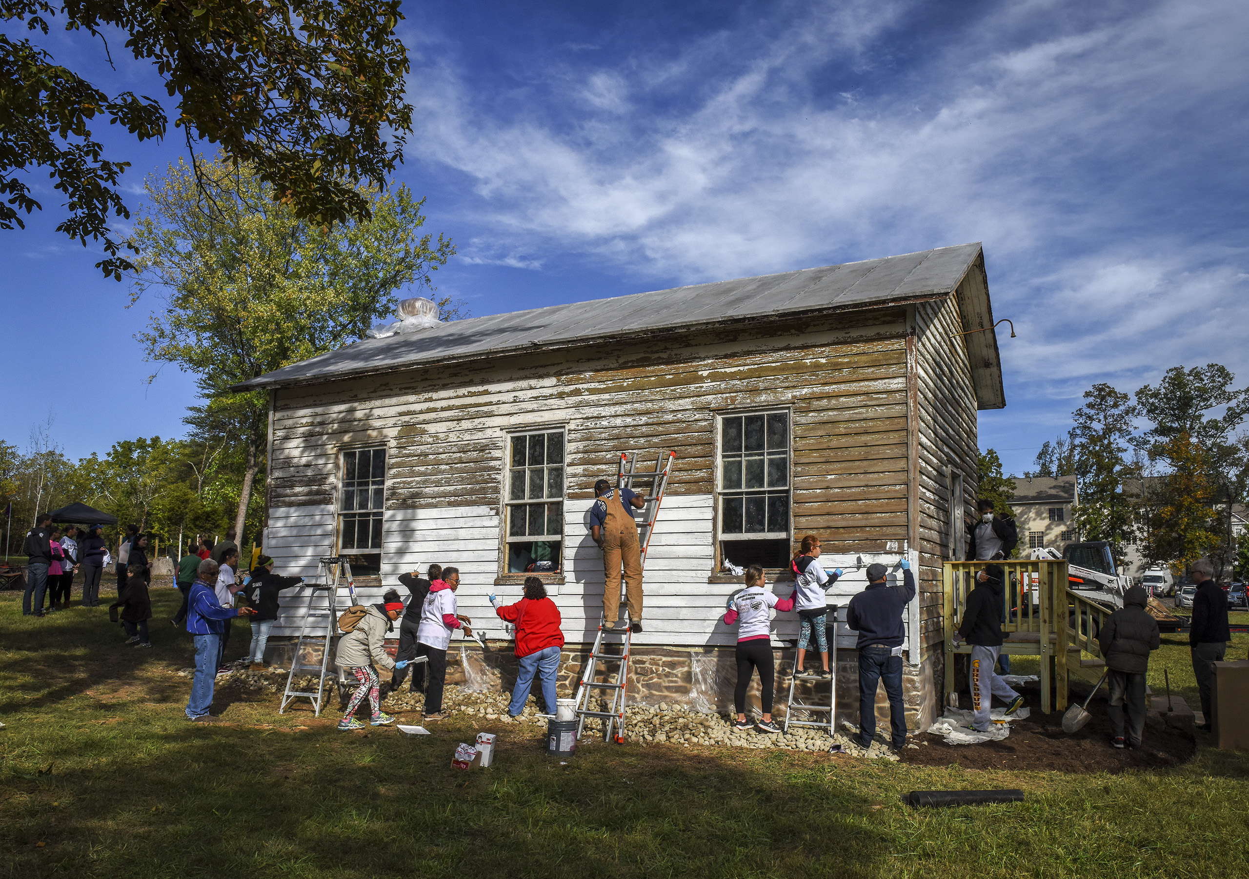 A group tackles painting the exterior as volunteers gather to restore the Ashburn Colored School, a nineteenth-century schoolhouse vandalized with racist symbols and hate language,  in Ashburn, VA on Oct. 9, 2016.
