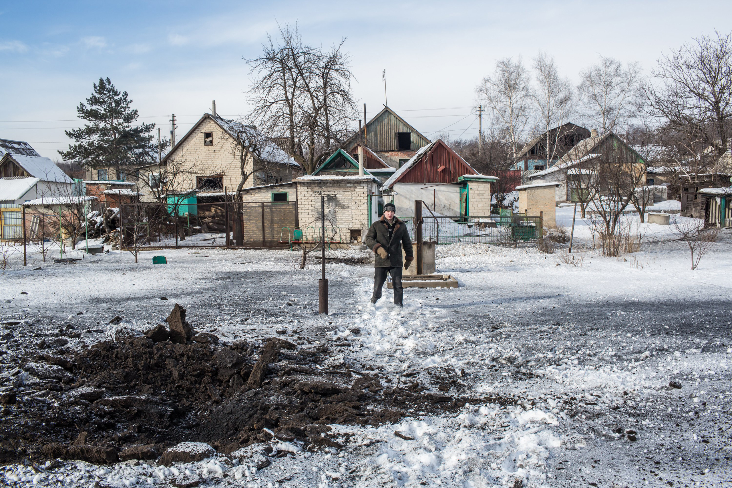 A man shows where one of six grad rockets landed in his backyard in Avdiivka, Ukraine, on Feb. 1, 2017.