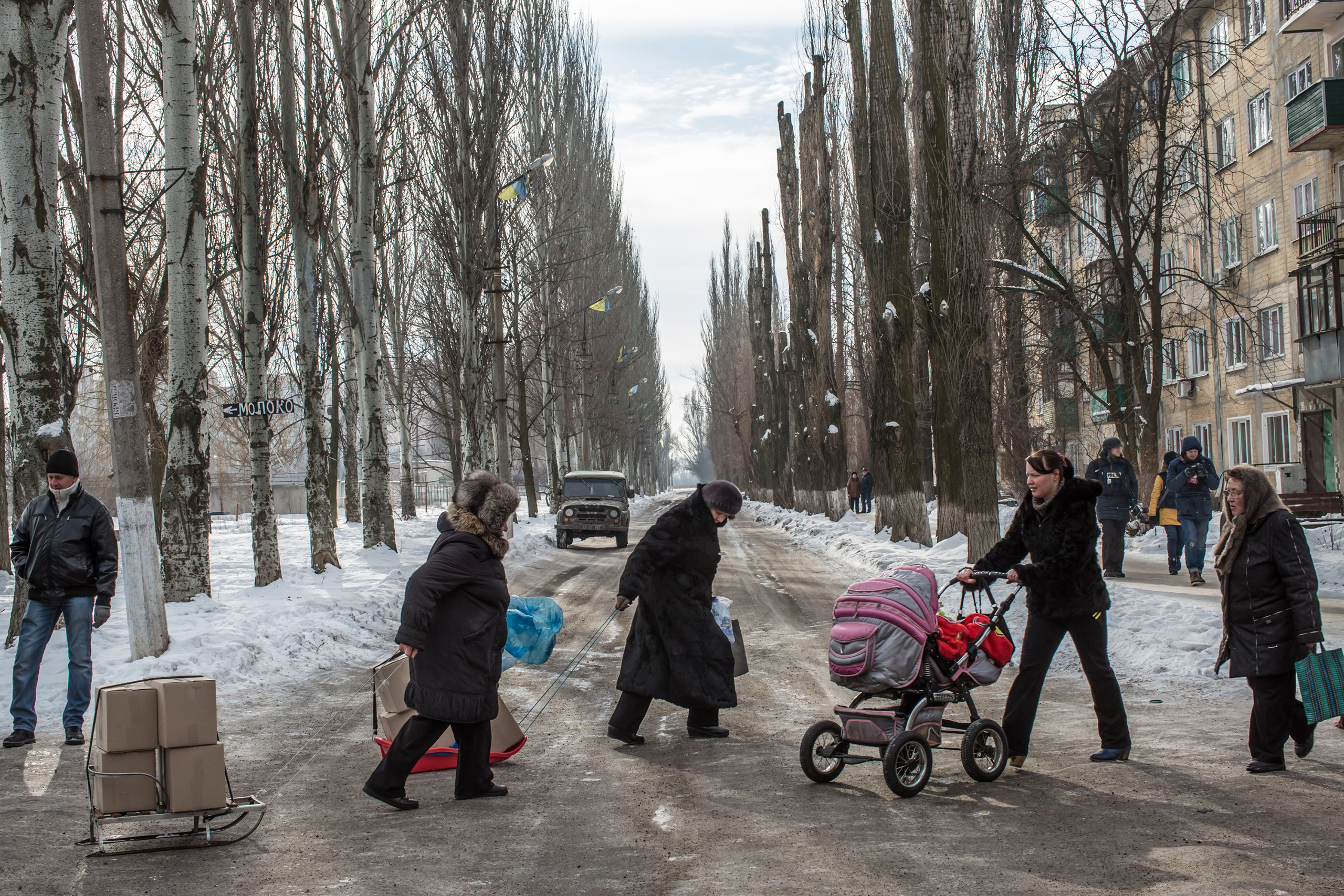 Residents carry boxes of humanitarian aid on sleds across the street after a night of shelling in Avdiivka, Ukraine, on Feb. 1, 2017.